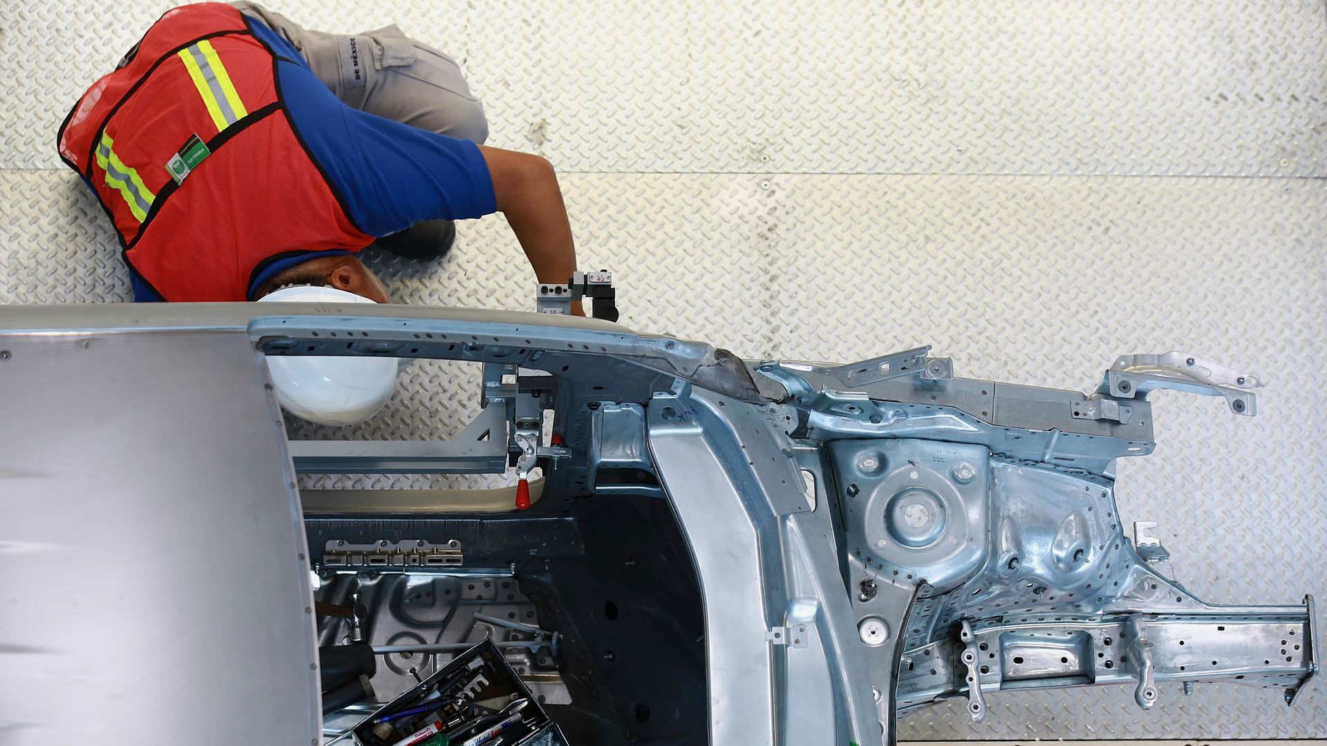 Employee works on test frame of car in Puebla, Mexico.