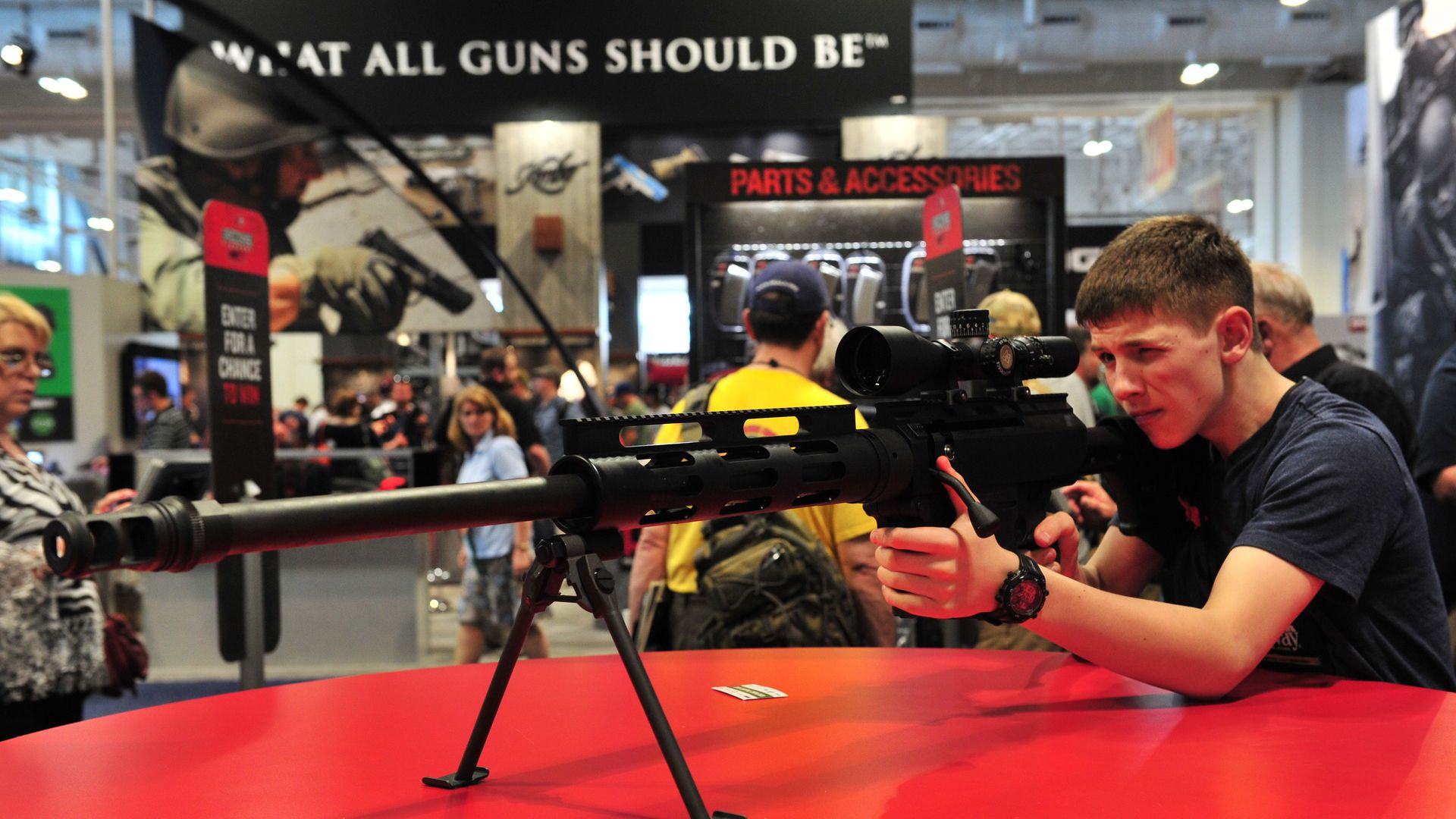 Man tries out Bushmaster rifle at gun show.