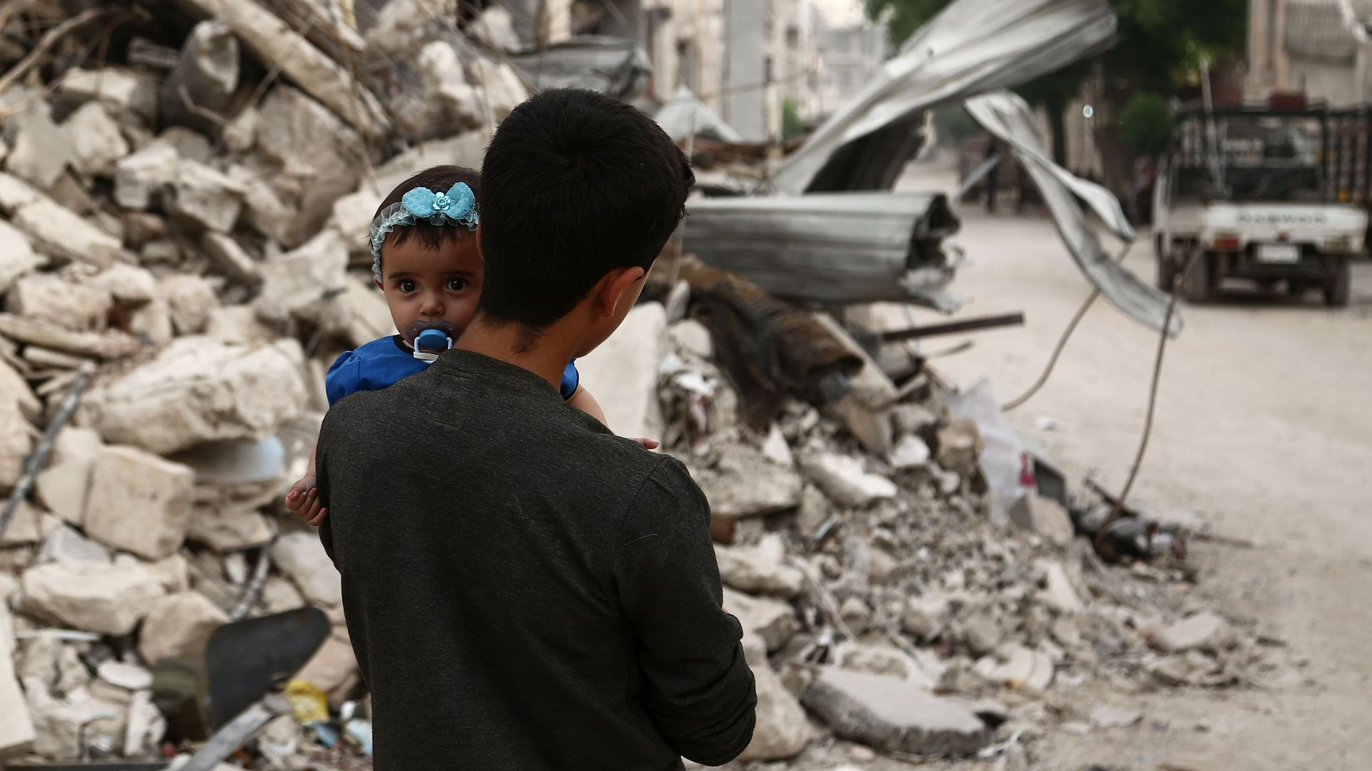 A Syrian youth walks by rubble holding a baby.
