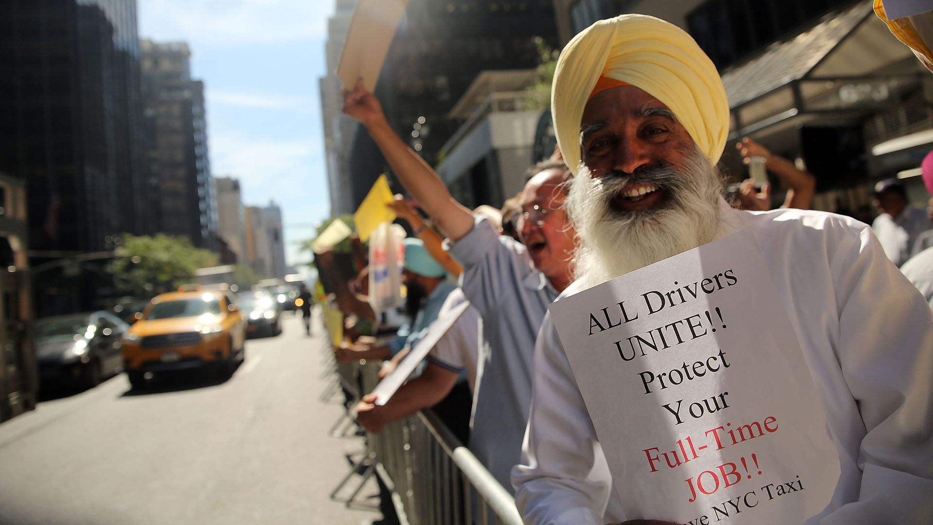 "NYC taxi drivers protesting. One holds a sign: ""ALL DRIVERS UNITE!! Protect your Full-Time JOB!"""