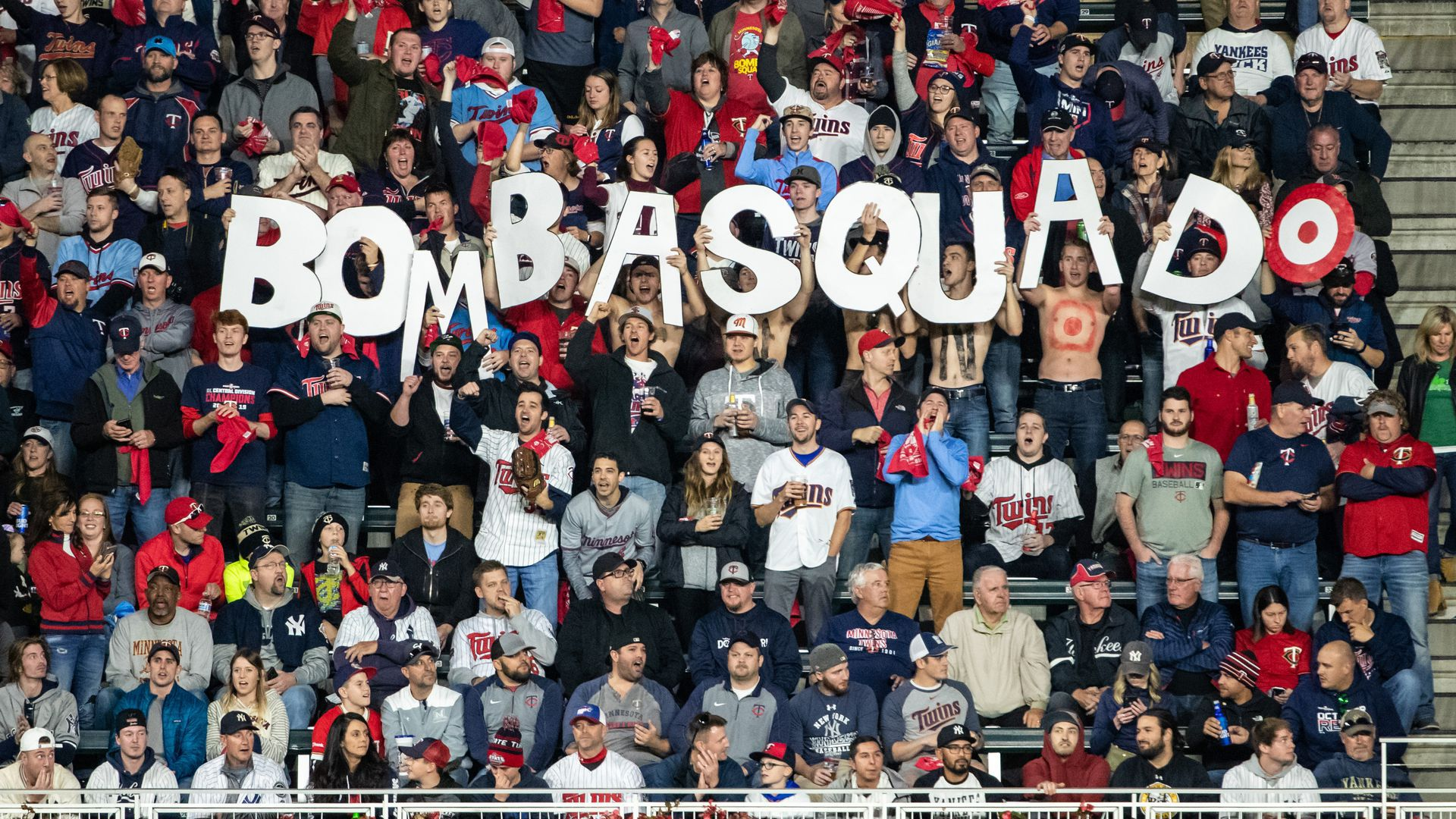 Minnesota Twins fans hold up letters spelling out Bombsquad at a game