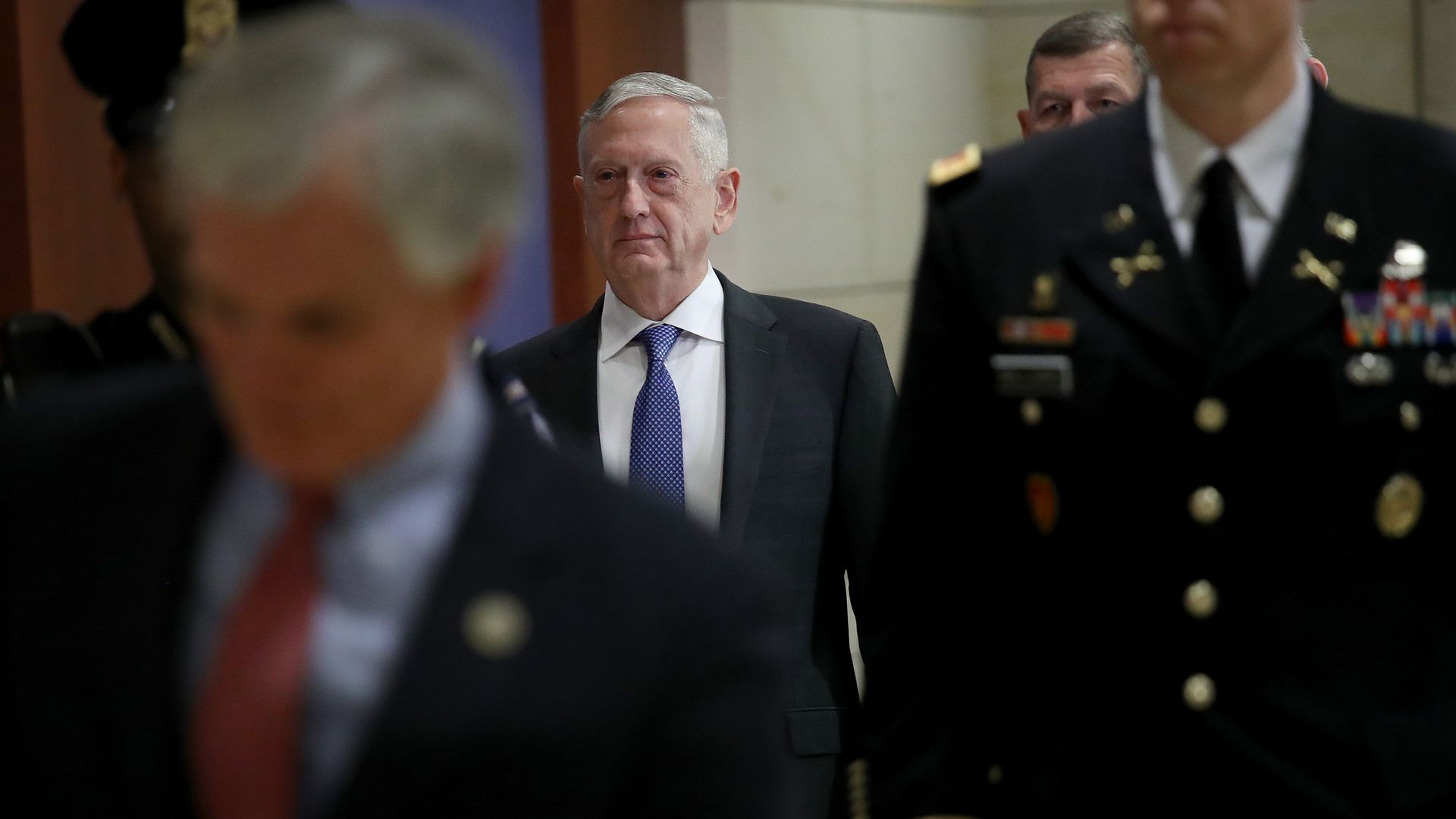 Jim Mattis walks down a hallway behind decorated and uniformed military personnel.