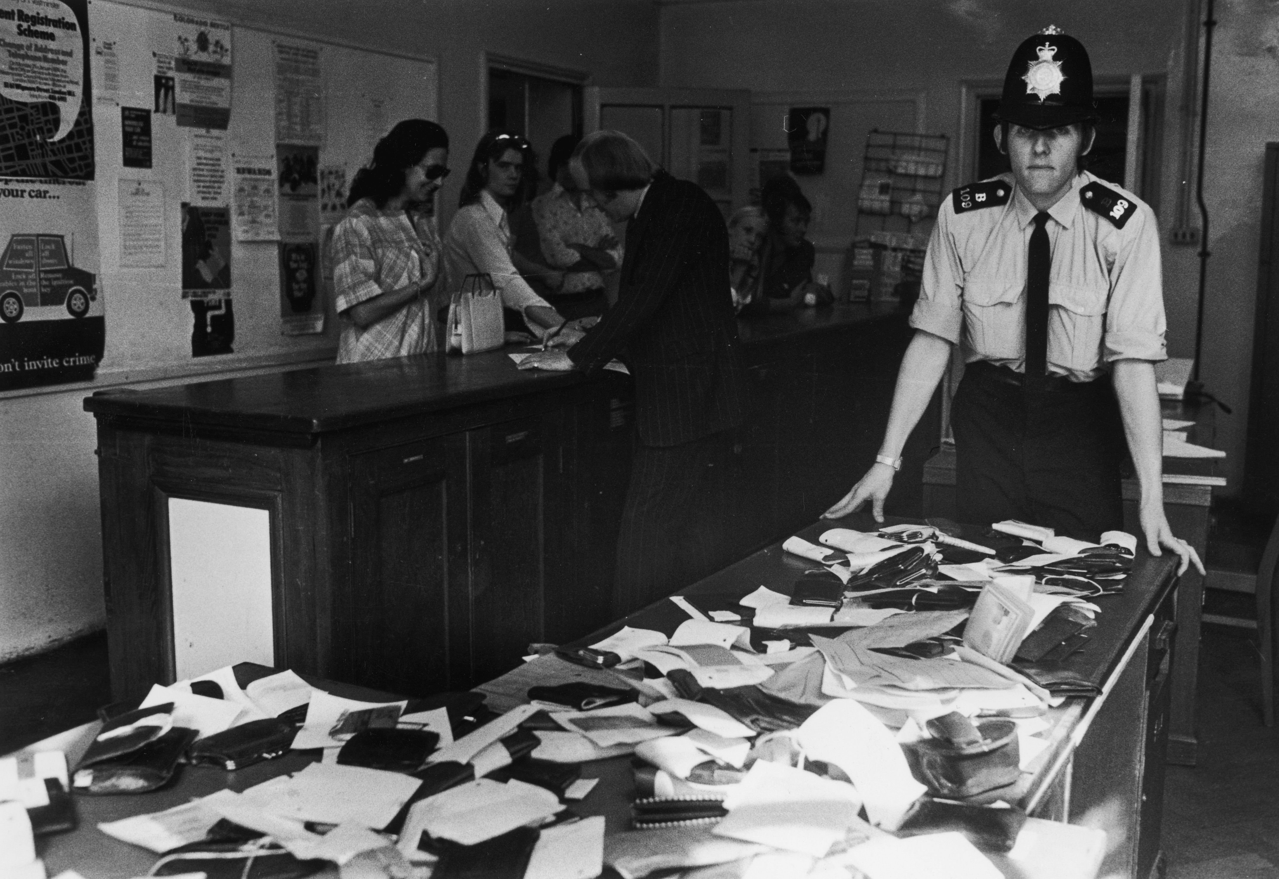 British policeman with a desk full of wallets