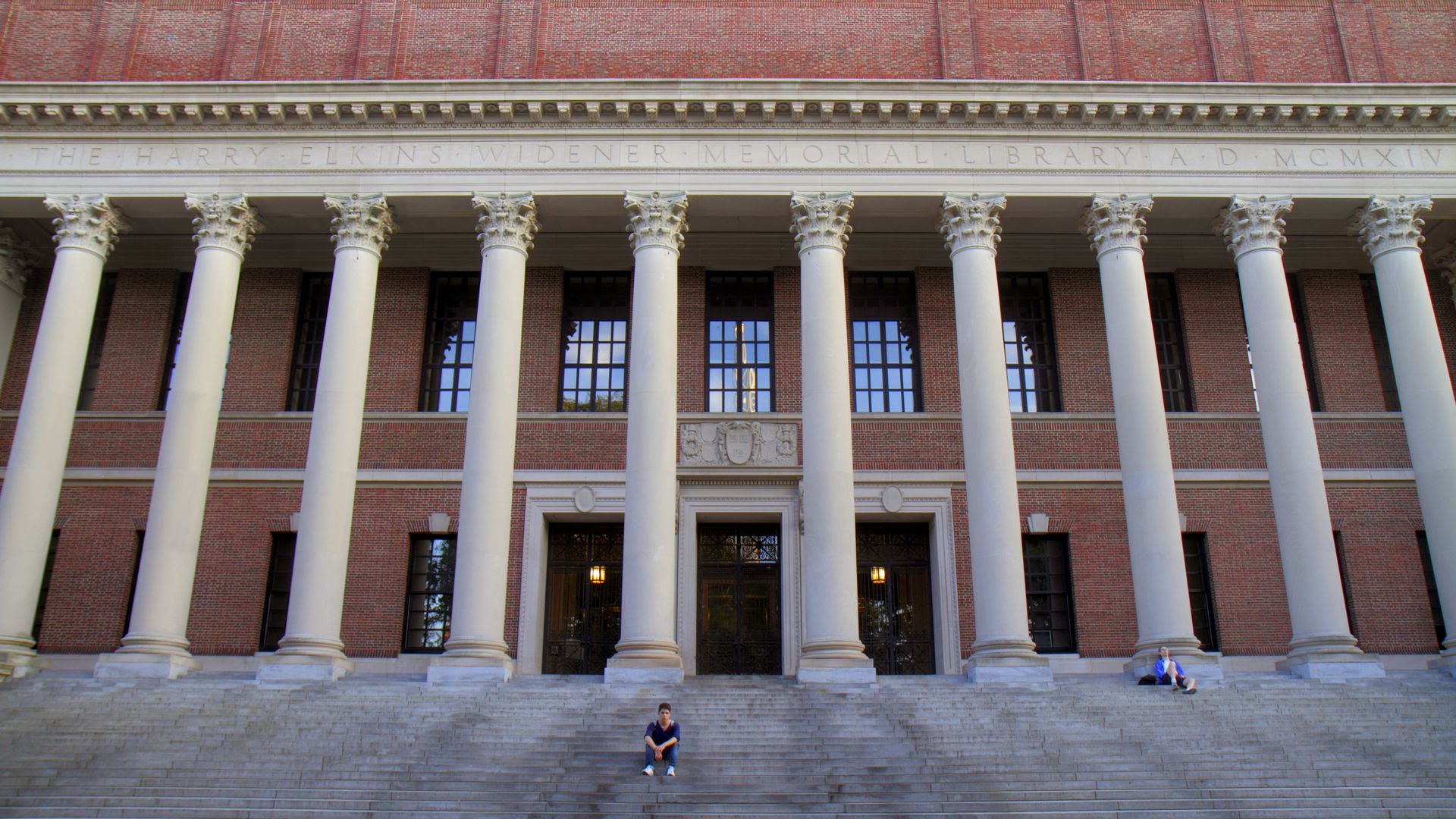 A student sits on concrete steps, wide shot