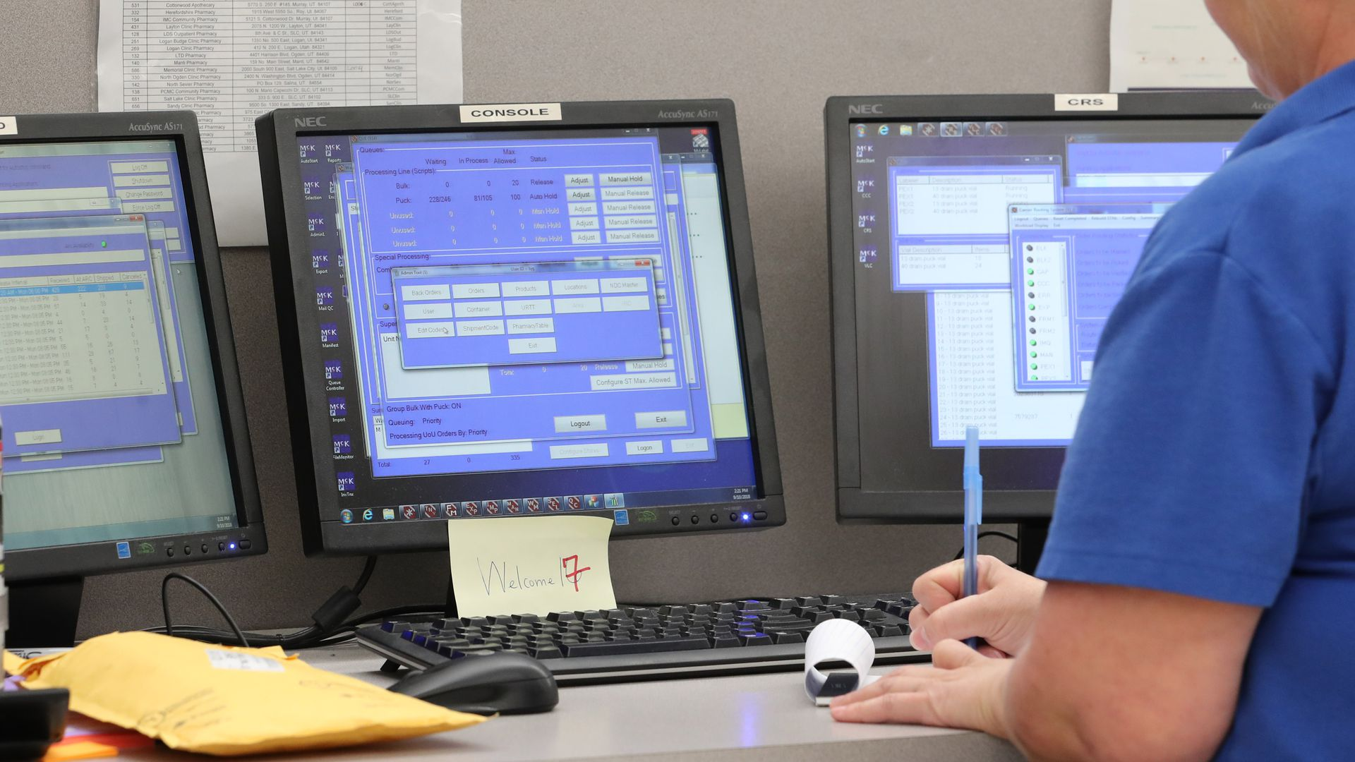 A pharmacy technician writes on a piece of paper in front of three computer screens.
