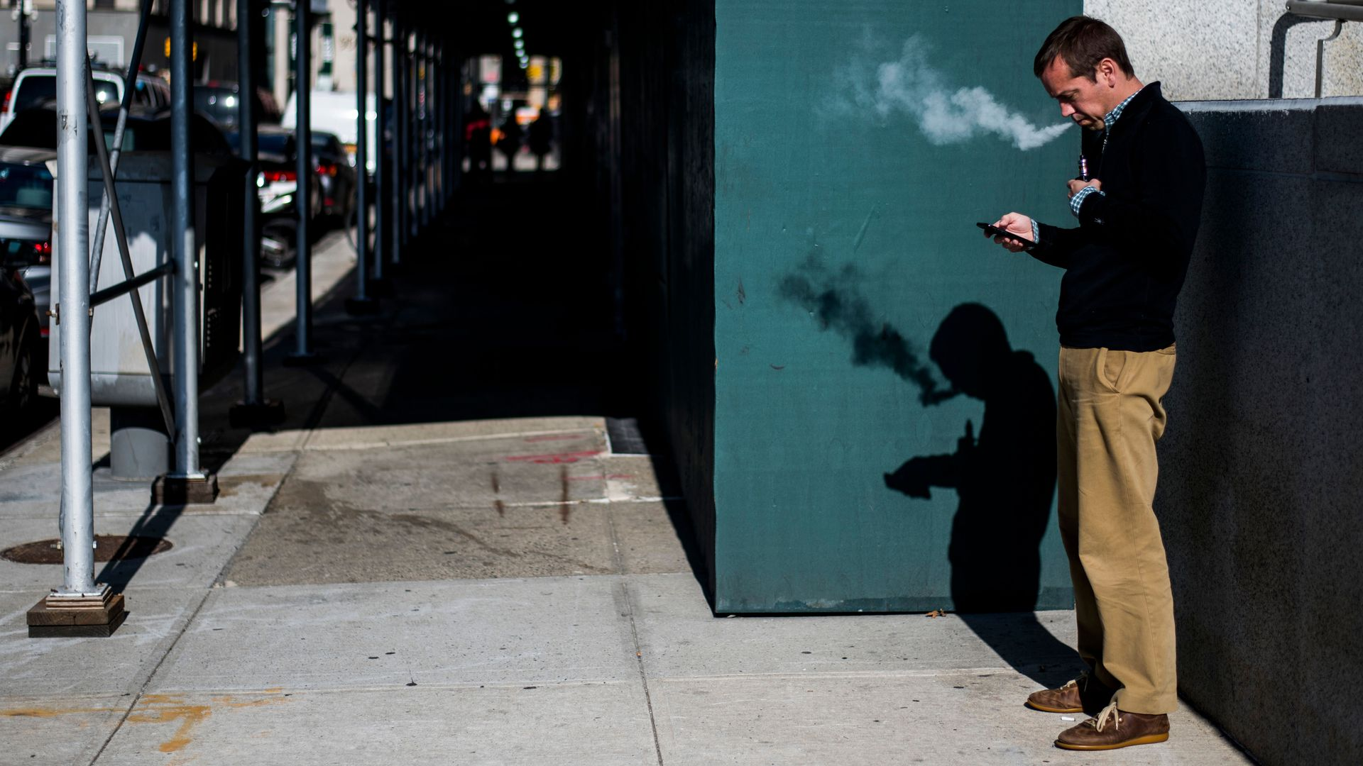 In this image, a man stands and looks at his phone while vaping on the sidewalk.