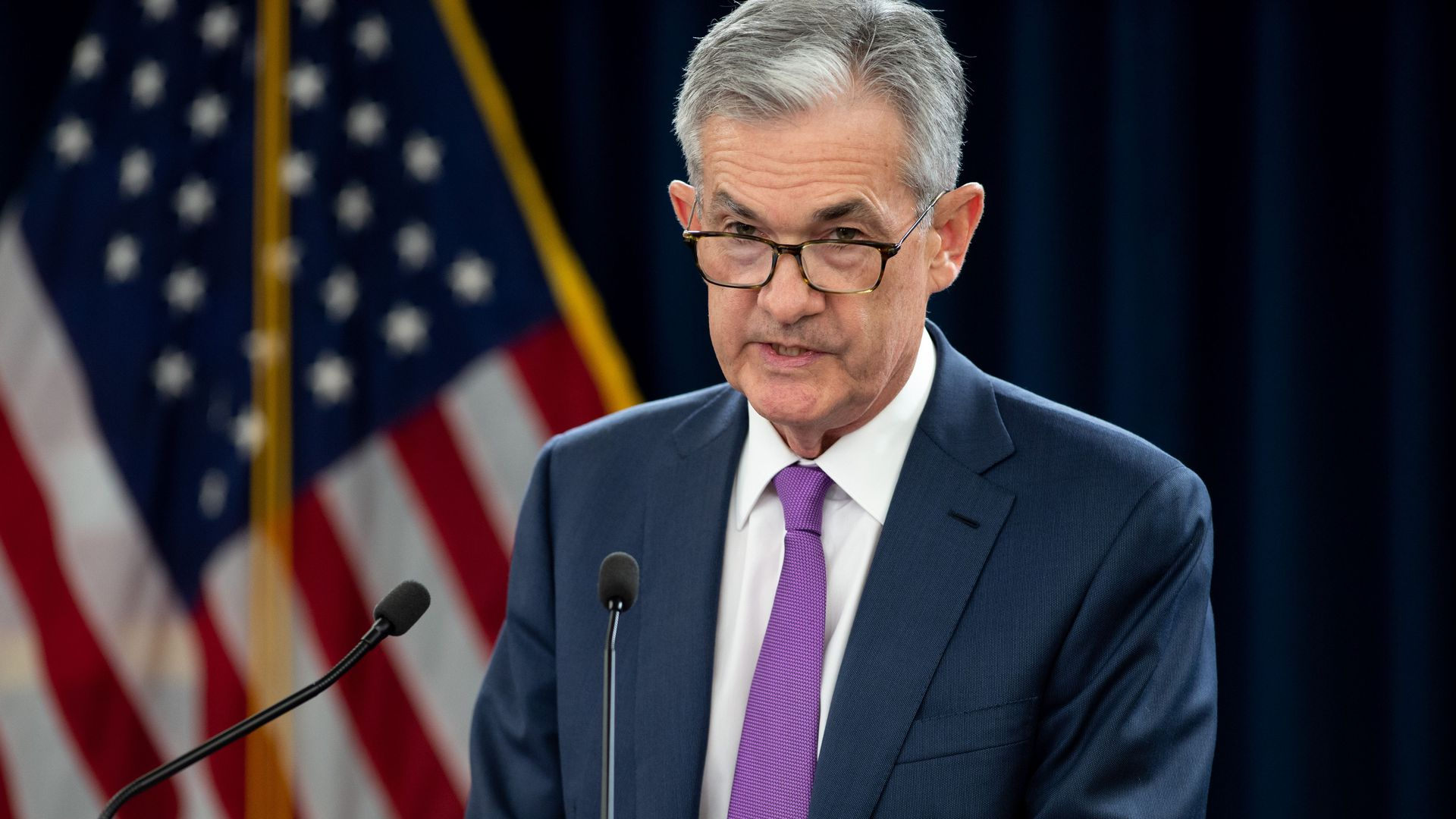 Federal Reserve Chairman Jerome Powell standing at a podium at a press conference.