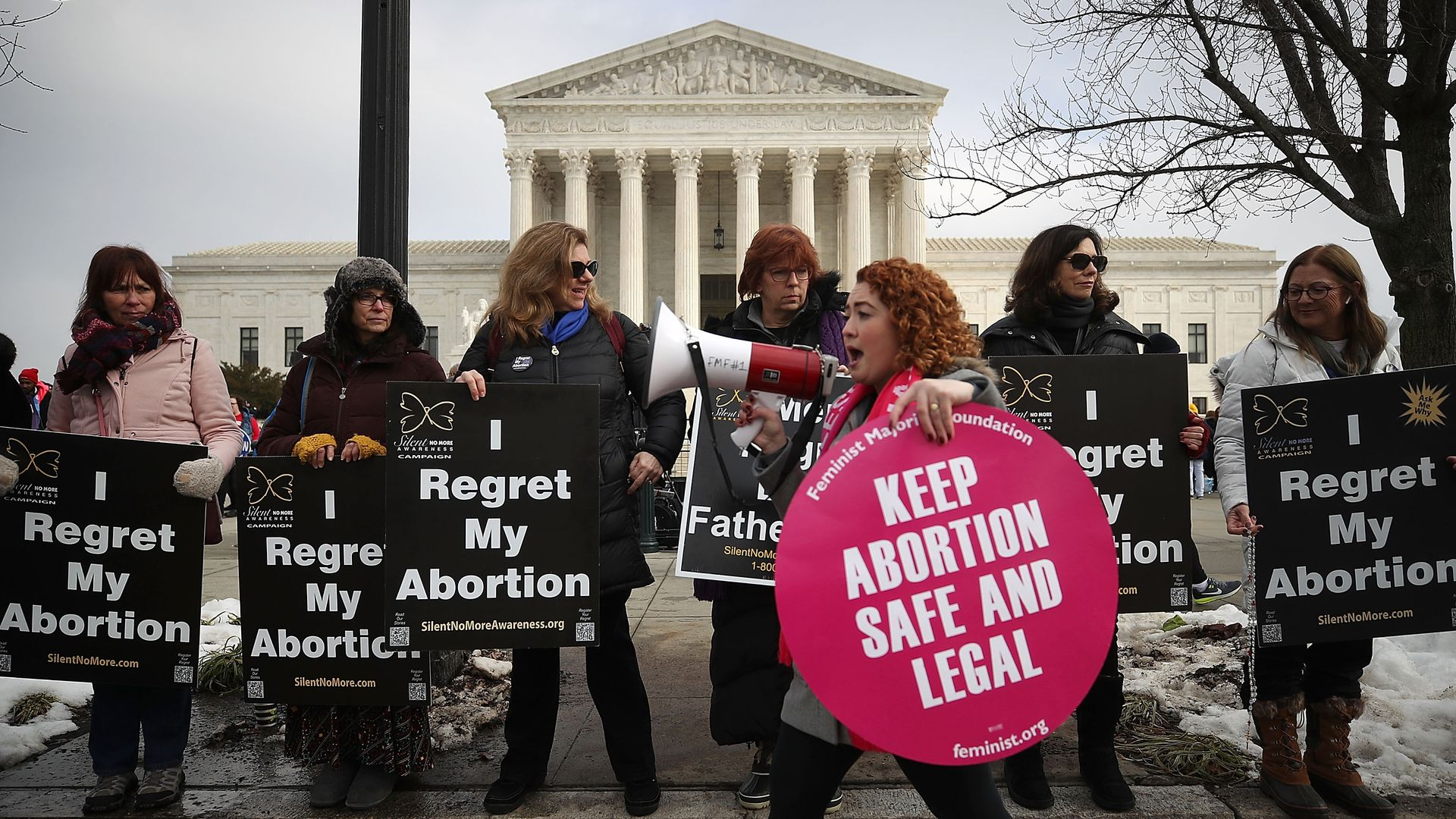 In this image, a pro-abortion protester walks past a line of anti-abortion protestors in front of the Supreme Court.