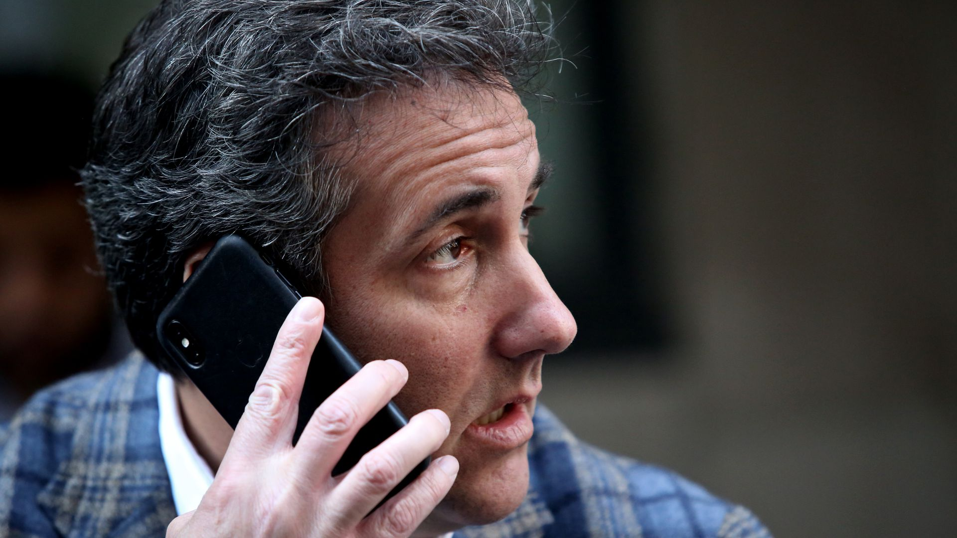 Michael Cohen holds a phone to his ear