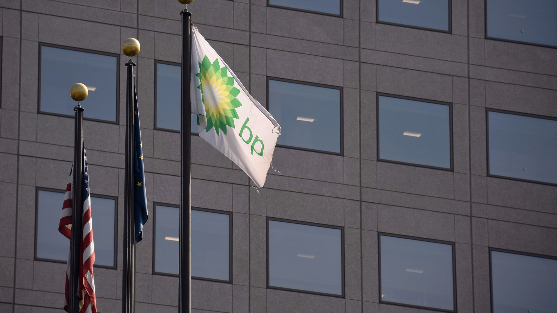 The American flag next to another flag and the flag of BP on a staff next to a building.