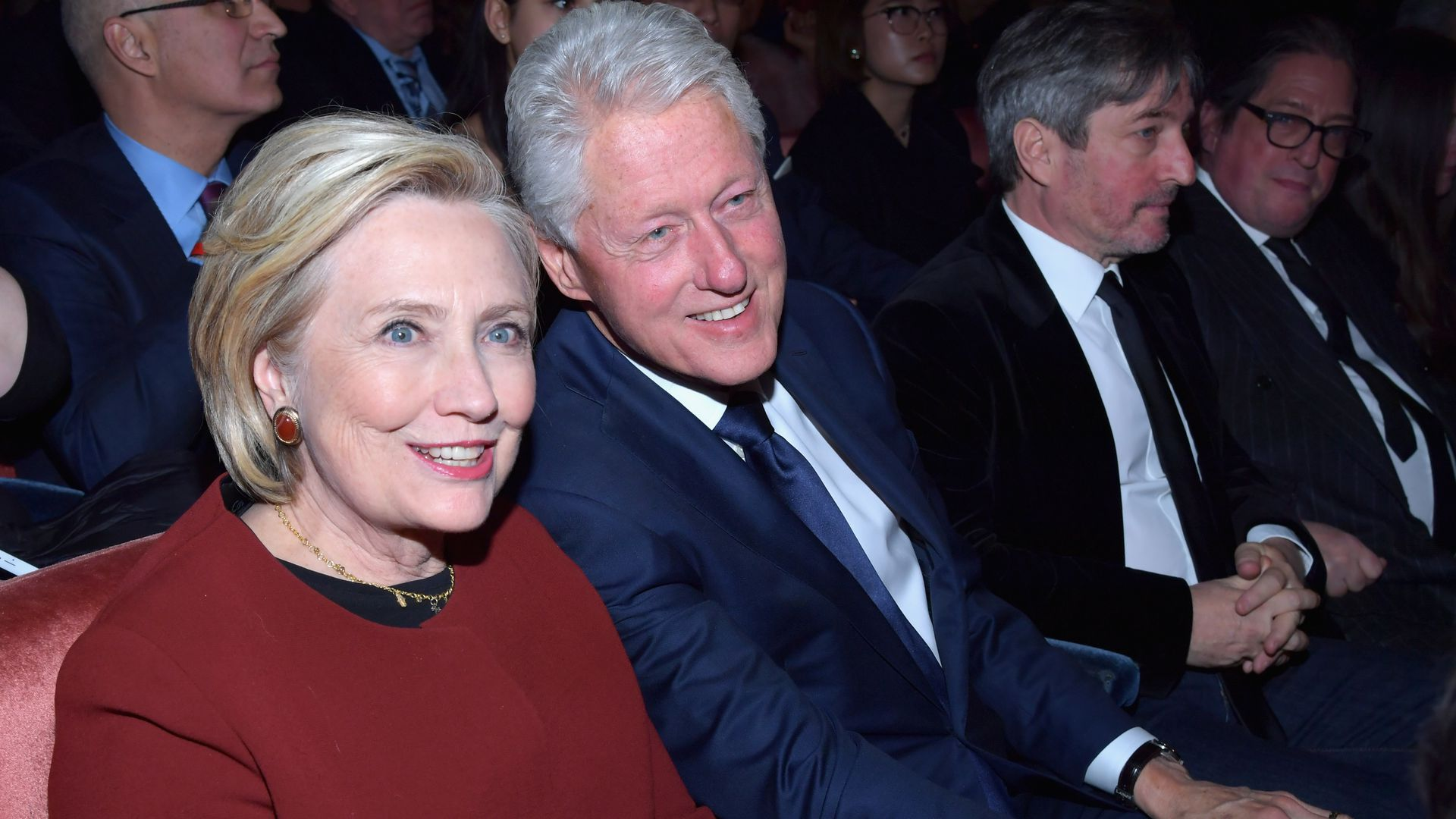Hillary and Bill Clinton sitting next to each other and smiling at the camera