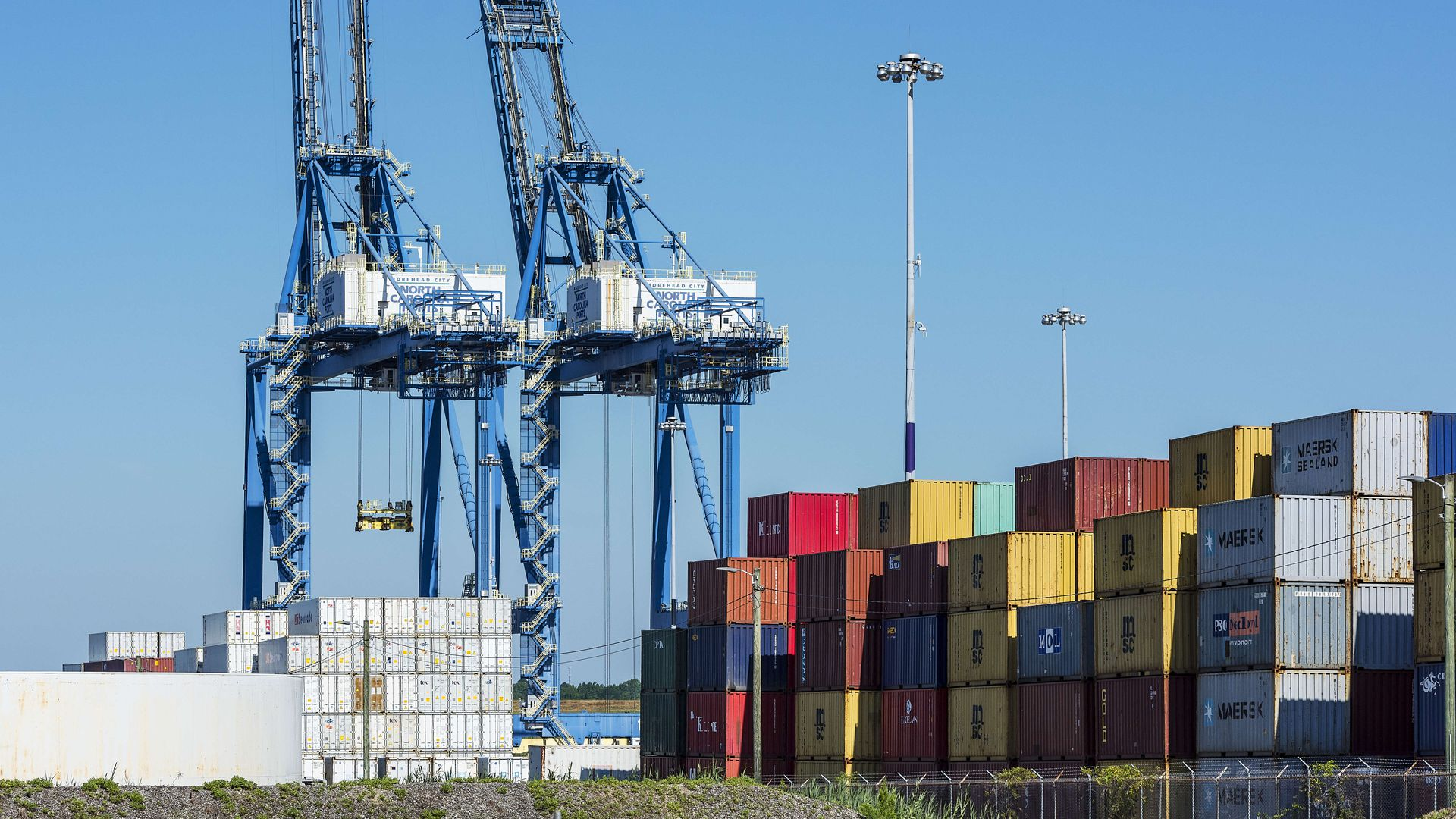 Brightly colored shipping containers and cranes at a port