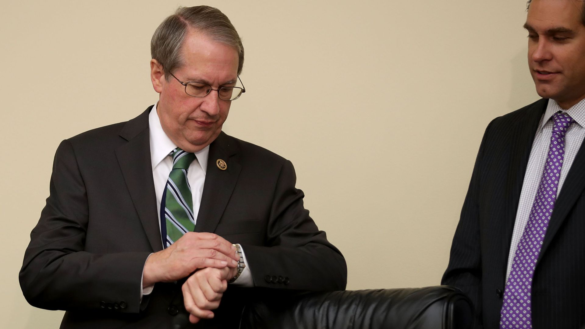 Bob Goodlatte checks his watching wearing a suit and tie