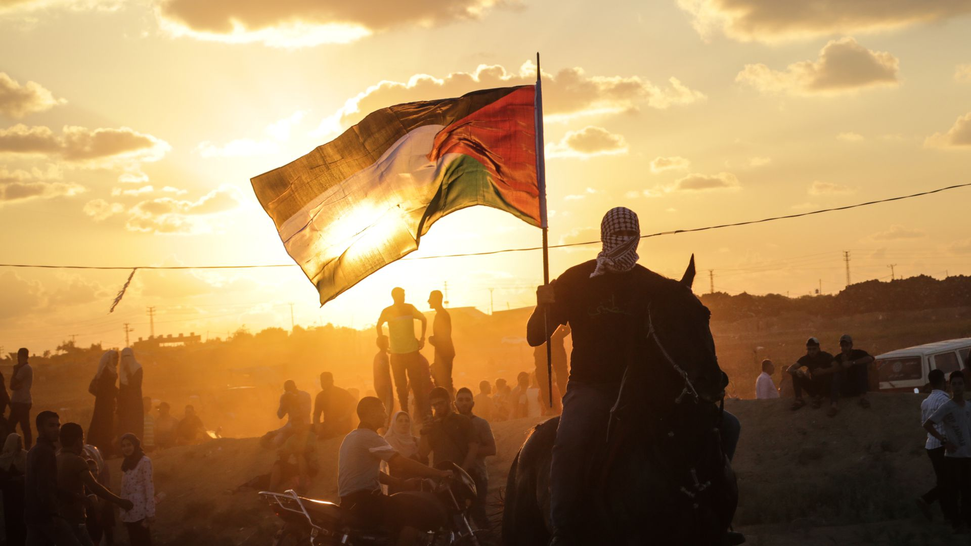 A Palestinian man riding a horse and waving a Palestinian flag during clashes between Palestinian protesters and the Israeli forces along the Israeli fence East of Gaza City.