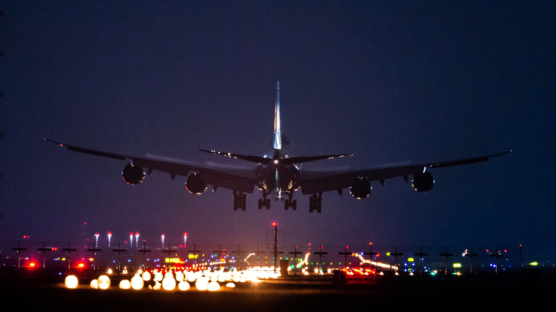 Airplane landing in dark sky.