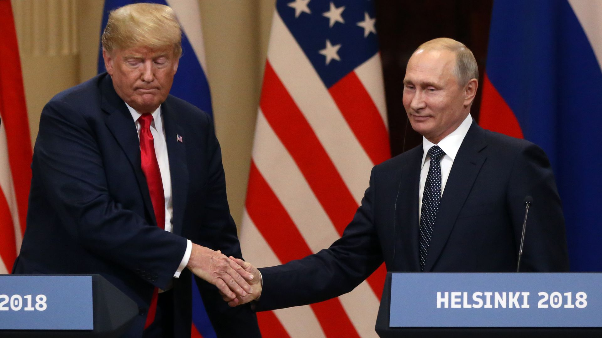 Trump and Putin shake hands while standing at podiums for press conference