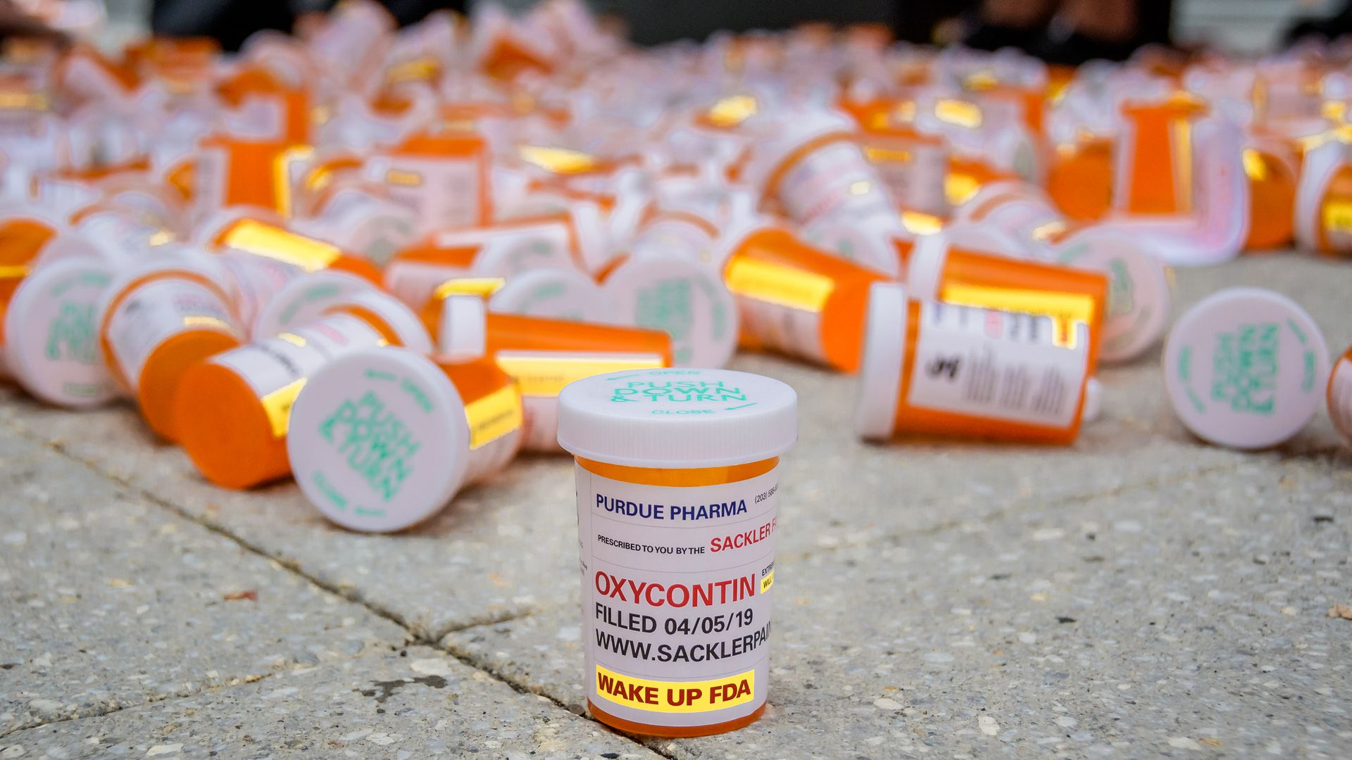 In this image, a pile of prescription bottles are piled on the concrete.