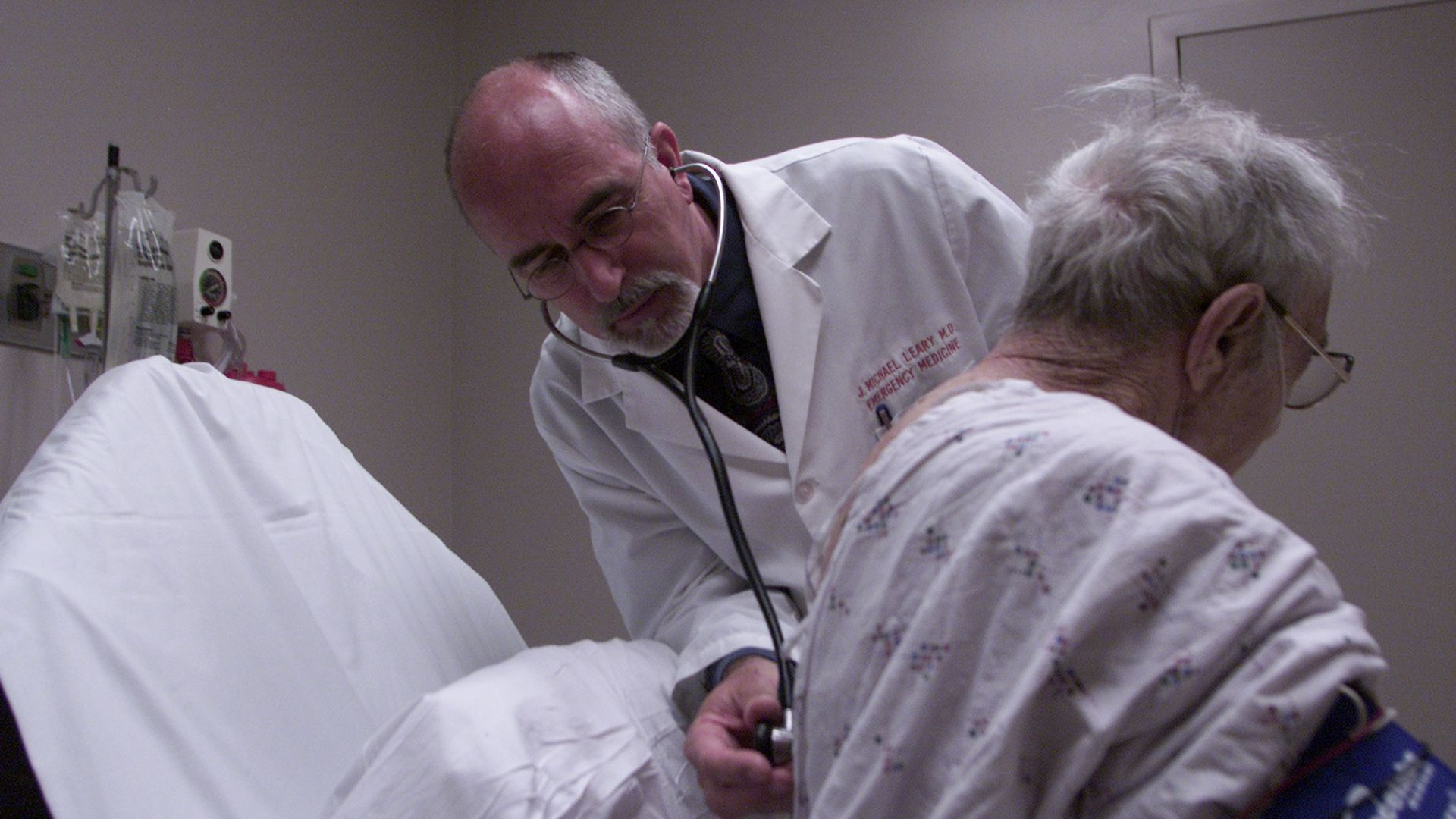 A doctor listens to an elderly patient