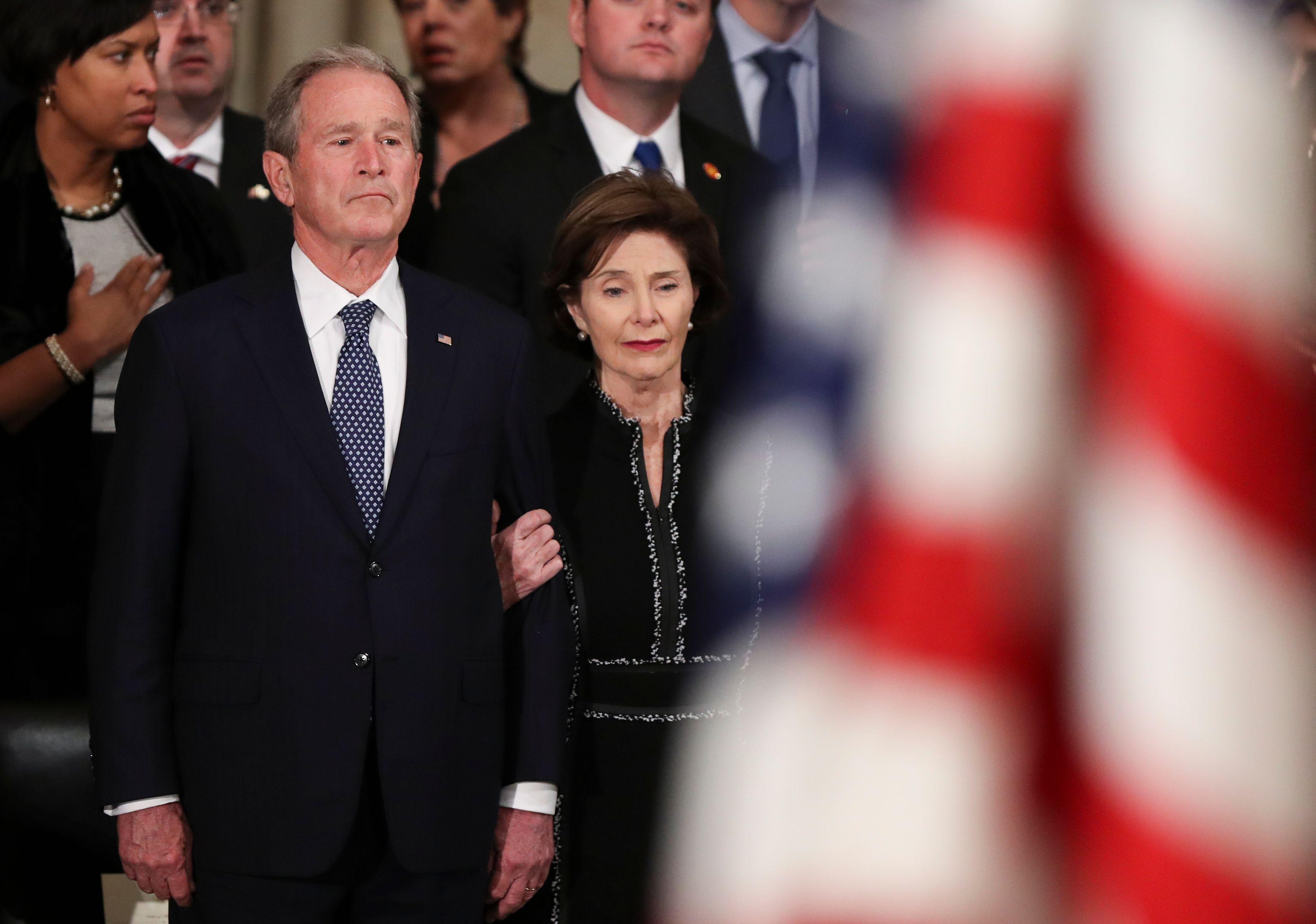 George W. Bush and Laura Bush look on sadly at George H. W. Bush's casket in rotunda.