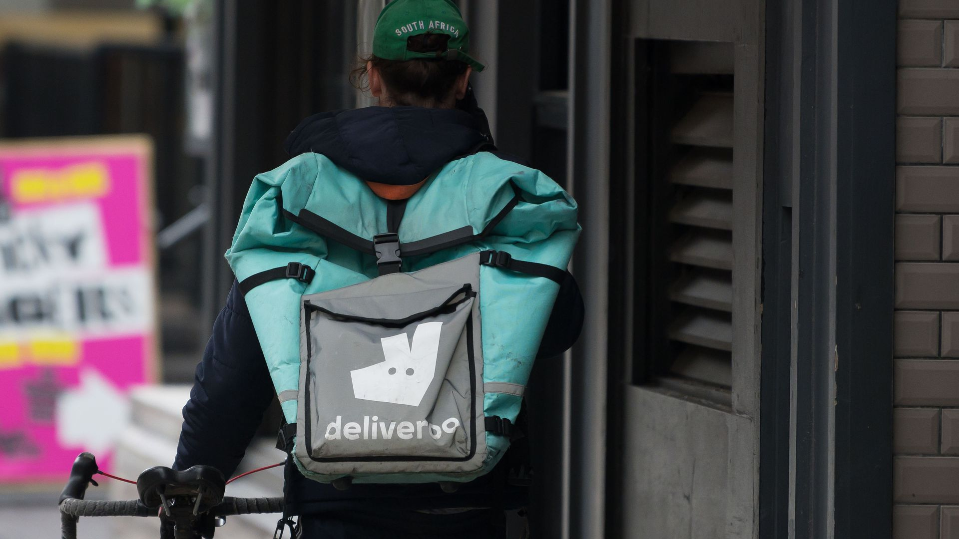 In this image, a Deliveroo deliveryperson walks down the street with a package on their back and guiding a bicycle.