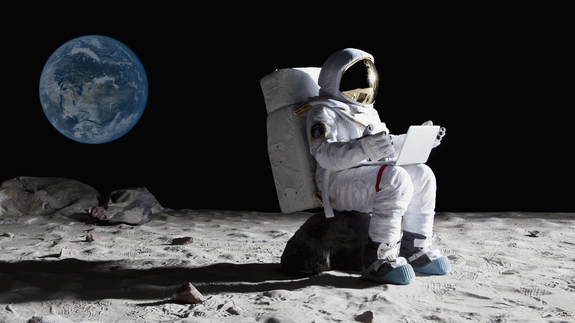 Man uses laptop while sitting on the moon.