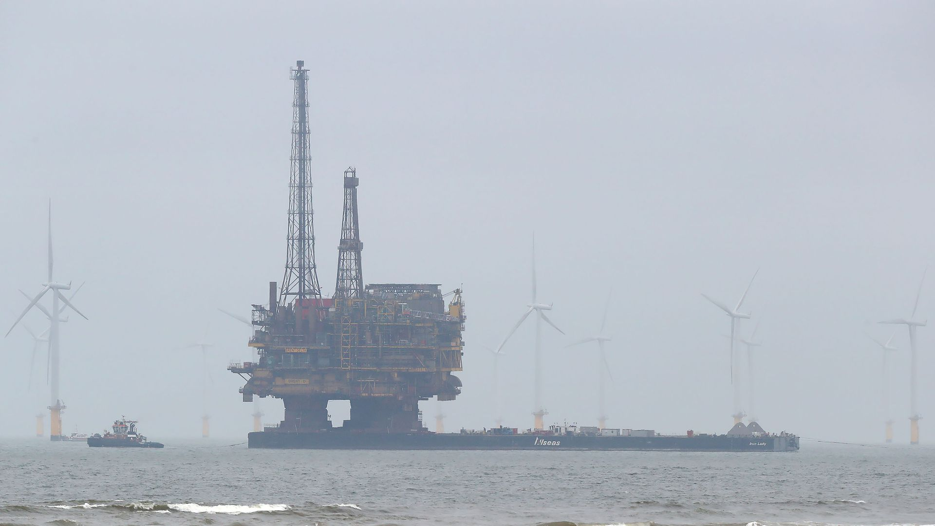 Shell oil rig surrounded by wind turbines