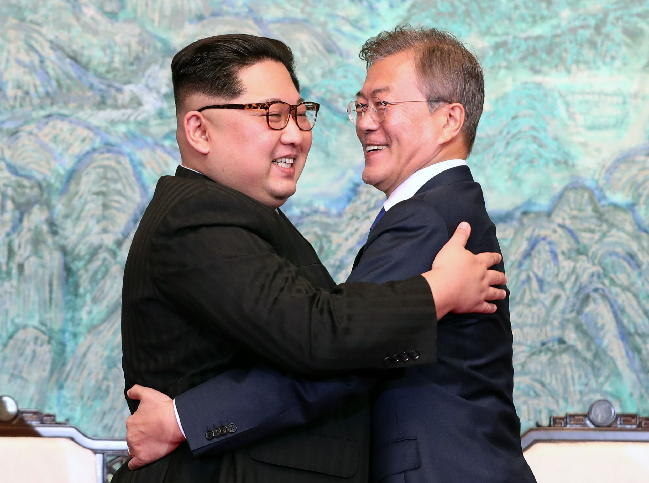 Kim Jong-un and Moon Jae-in hug each other before a blue-green background.