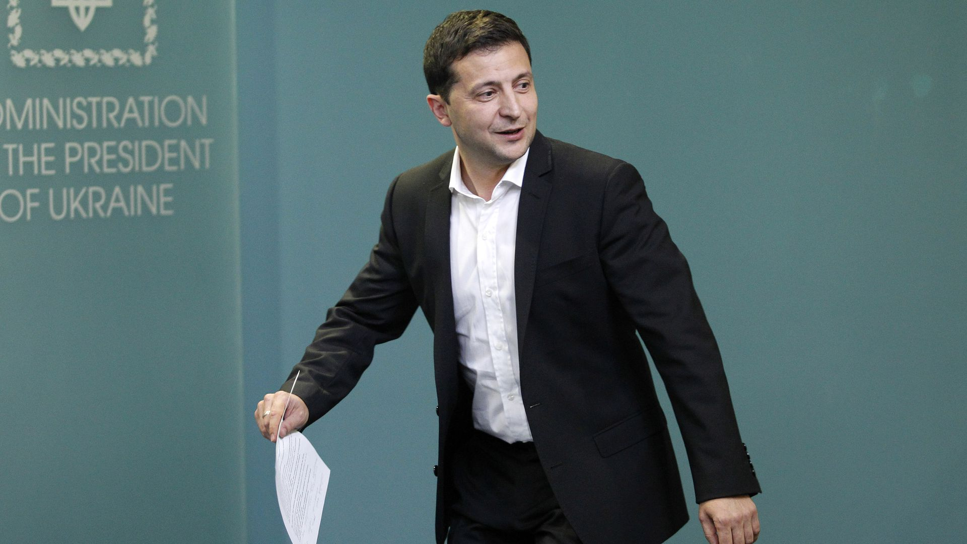 In this image, Zelensky walks while holding a piece of paper.