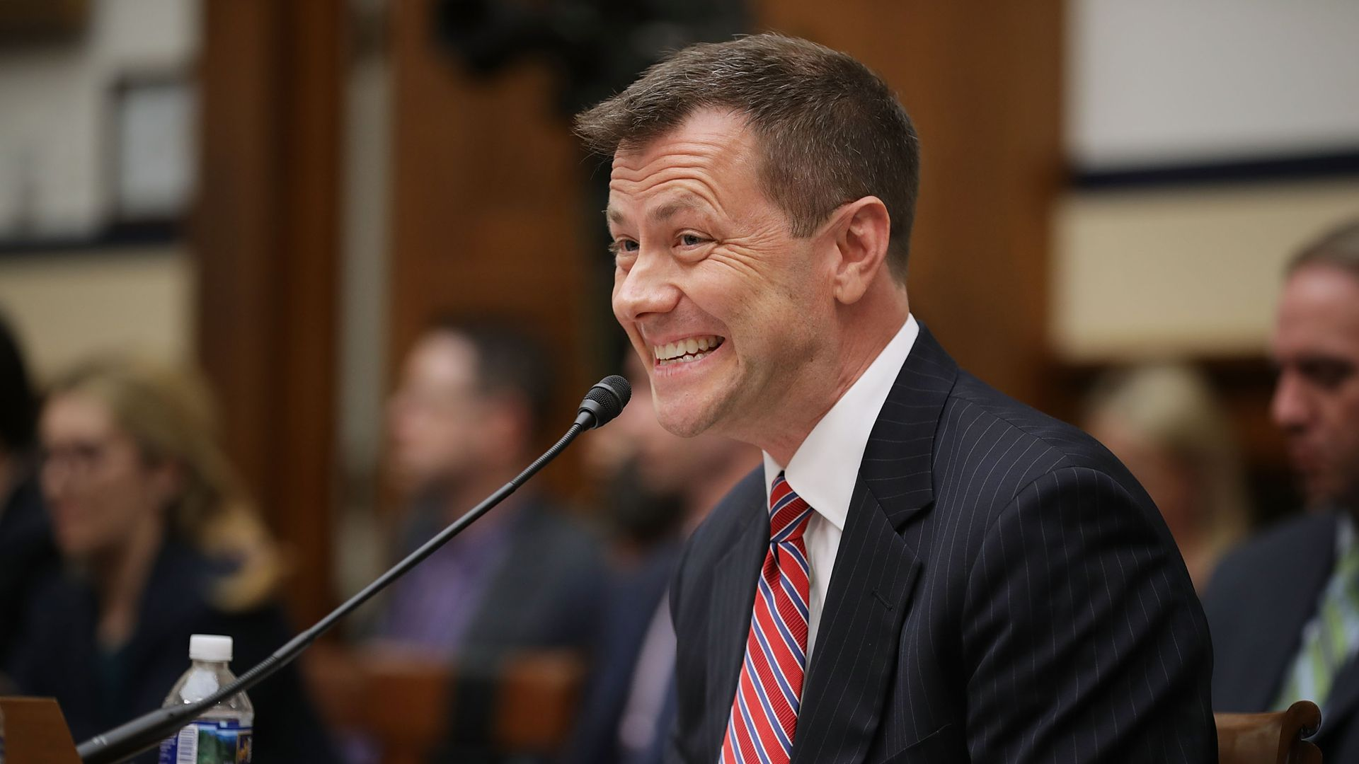 Peter Strzok testifying to Congress grimaces into a microphone