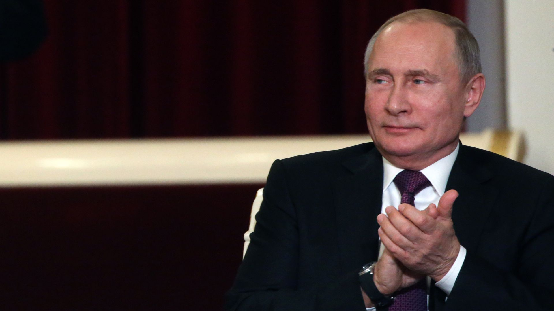 Vladimir Putin glances to his right while clapping his hands together