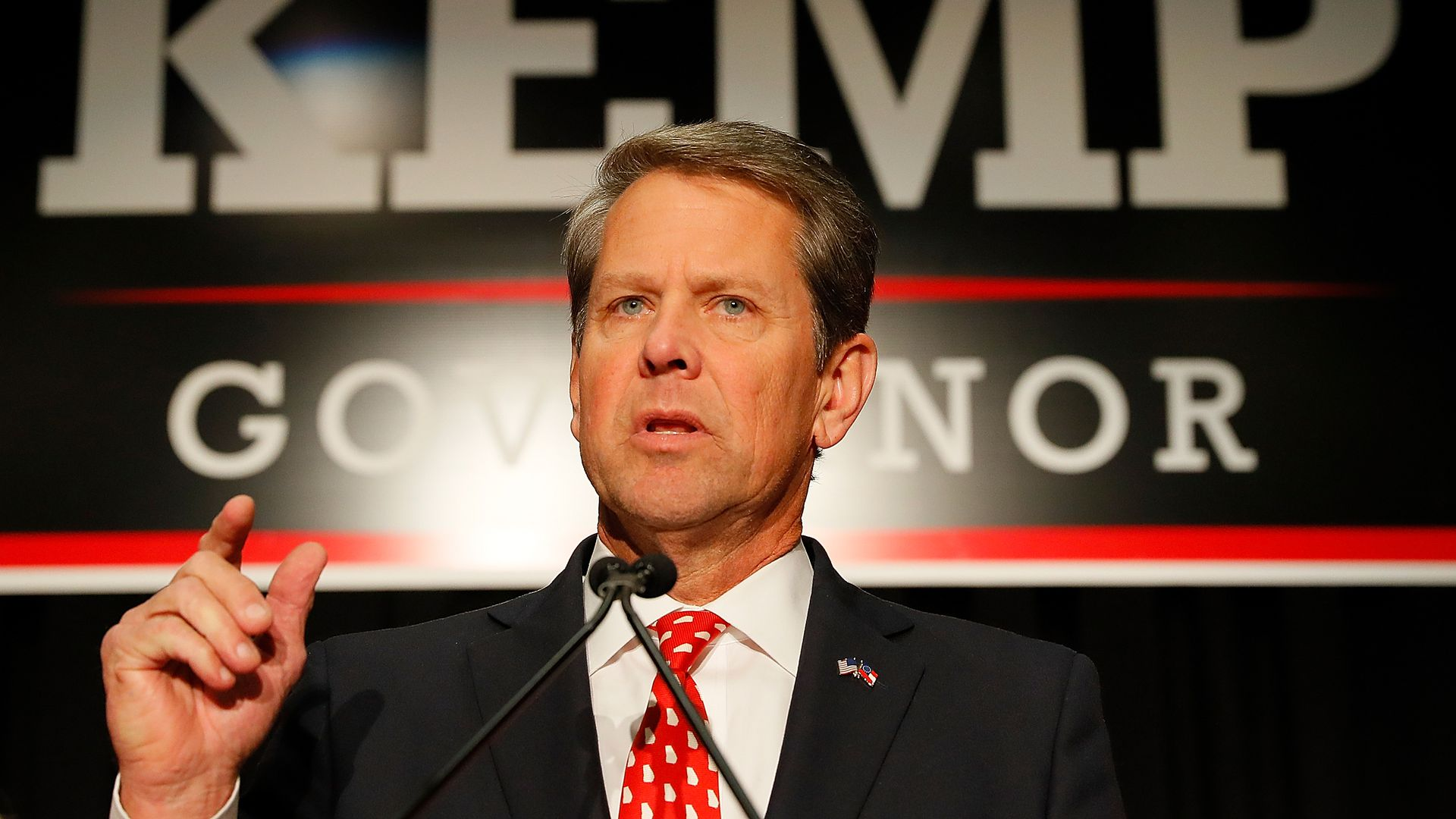 """Brian Kemp speaks with a """"kemp for governor"""" sign in the background."""