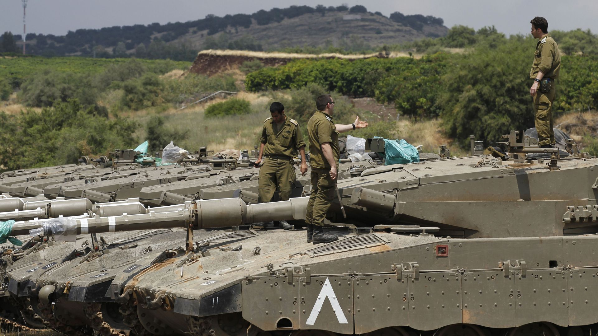 sraeli soldiers stands on top of Merkava Mark IV tanks as troops take position near the Syrian border in the Israeli-annexed Golan Heights on May 9, 2018