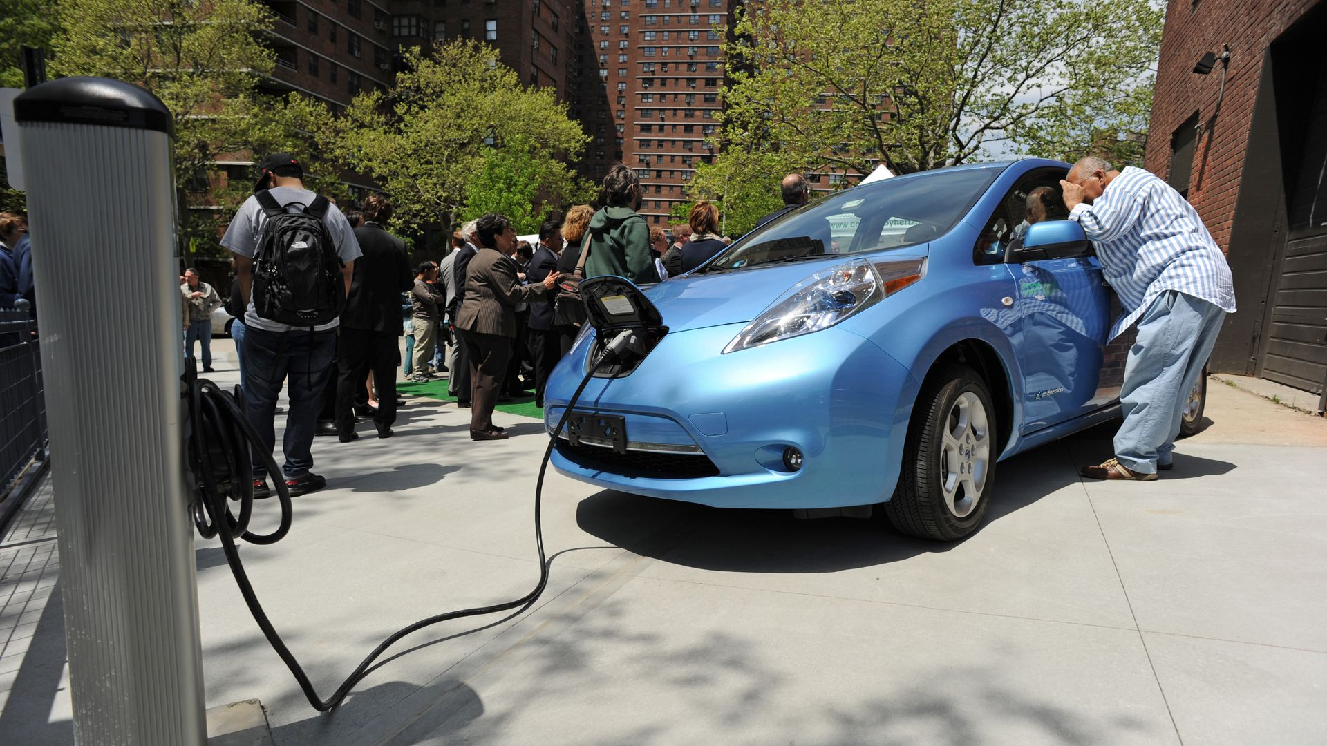 A man looks into a Nissan Leaf electric car t on the Lower East Side of Manhattan May 6, 2011 in New York.