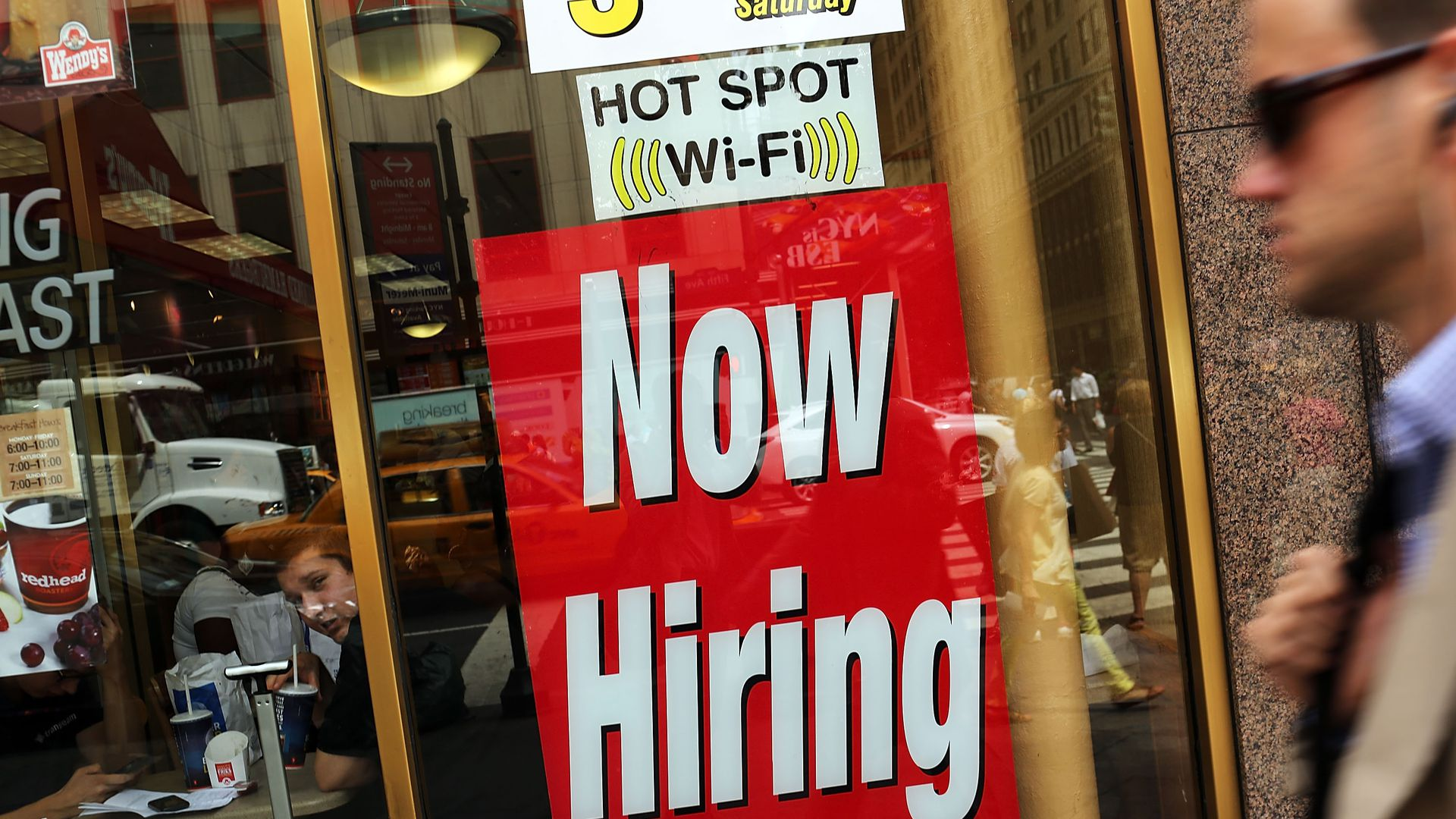 Photo of Now Hiring sign in store window