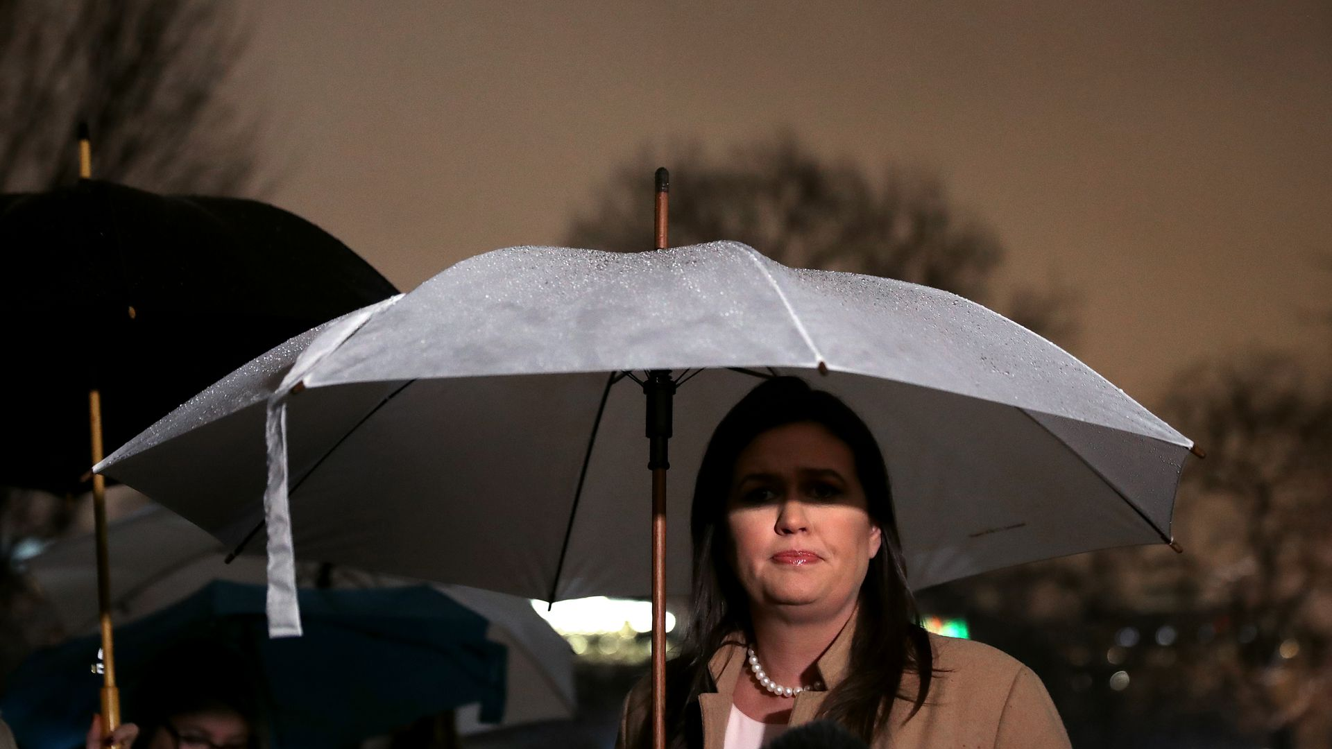 Sarah Sanders holding an umbrella over her head so that it shades part of her eyes