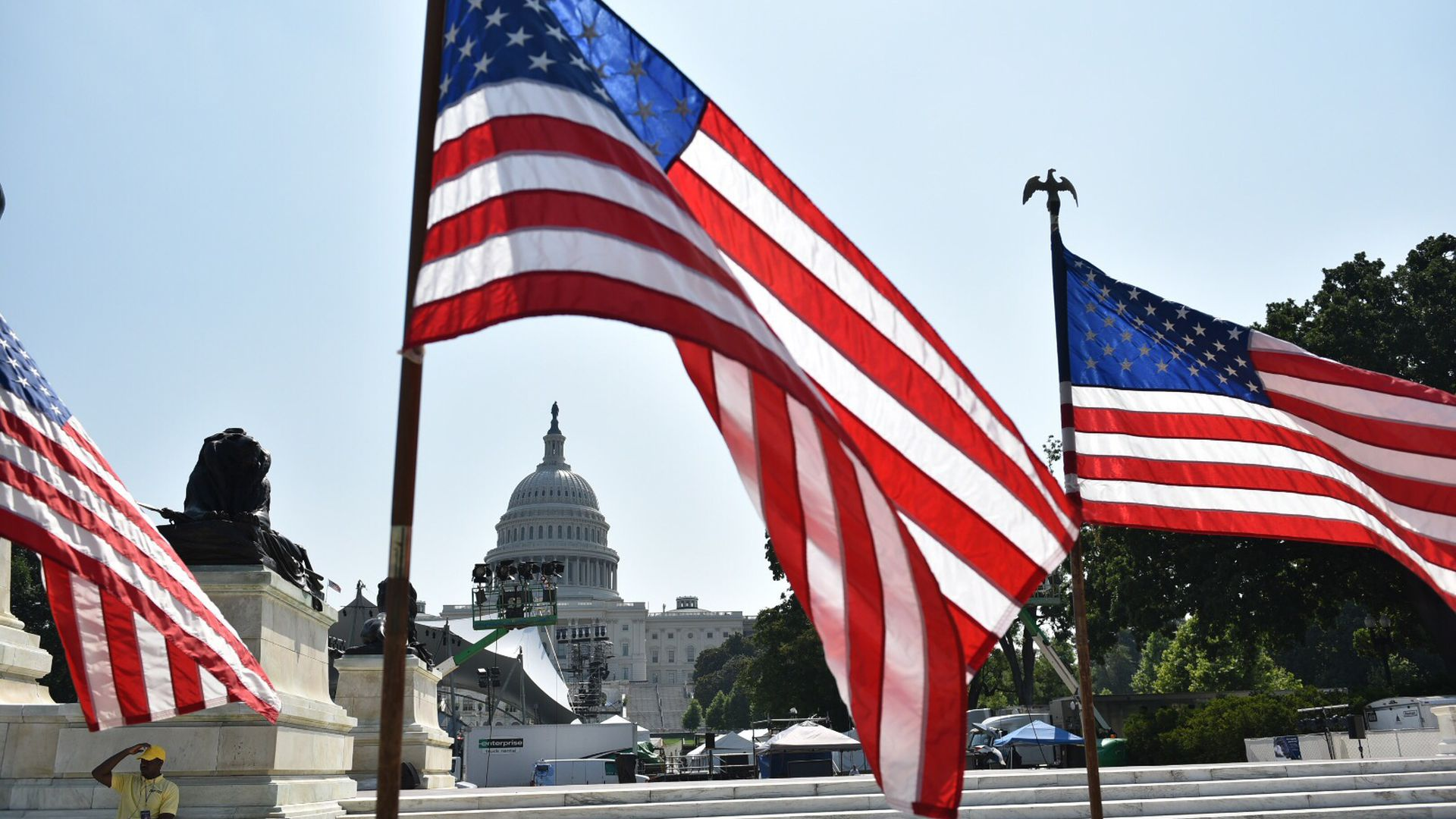 U.S. flags fly in front of the Capitol building.