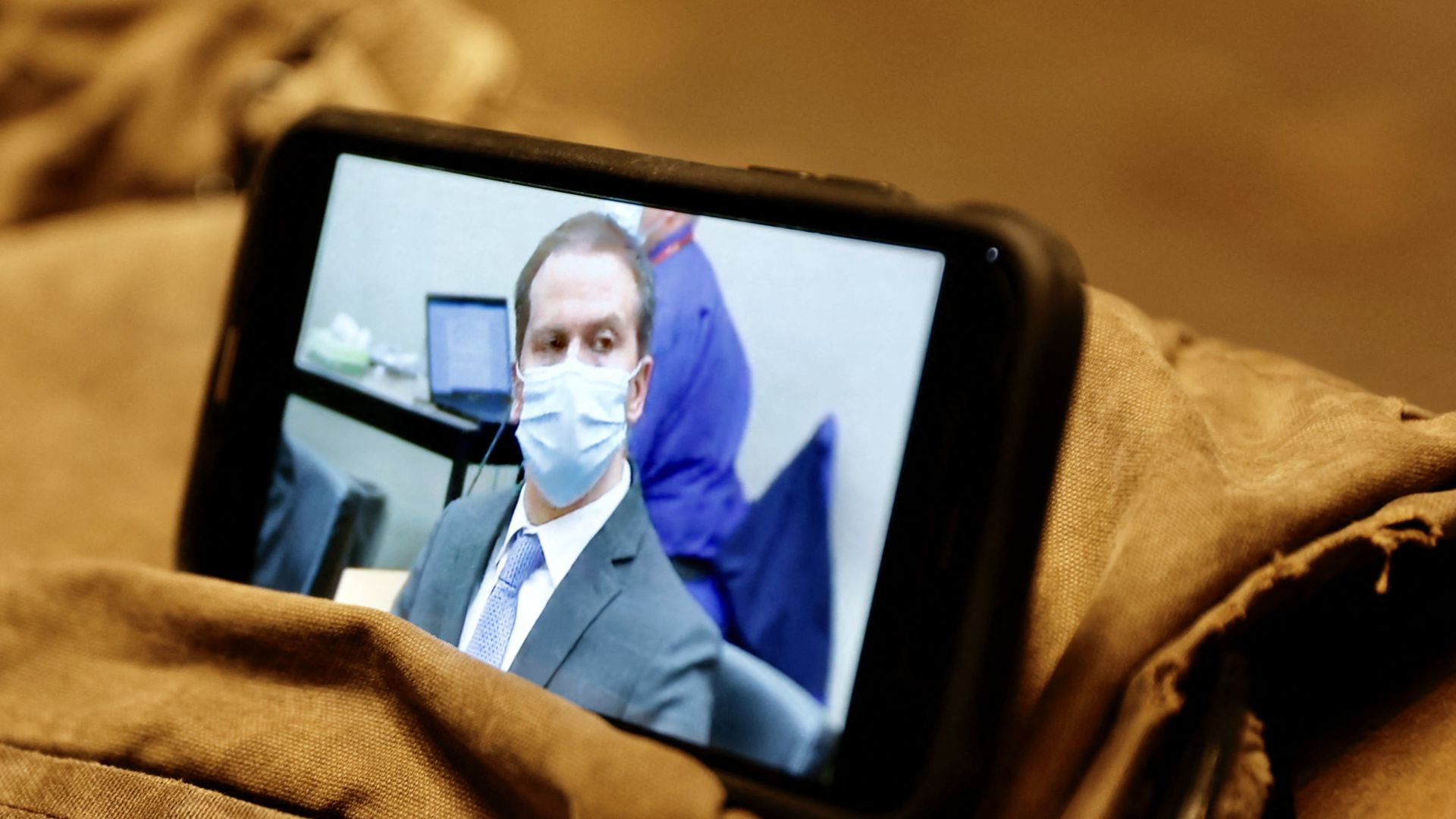 A journalist watches their mobile phone showing Derek Chauvin as the verdict in his trial over the death of George Floyd is announced in Minneapolis, Minnesota on April 20, 2021
