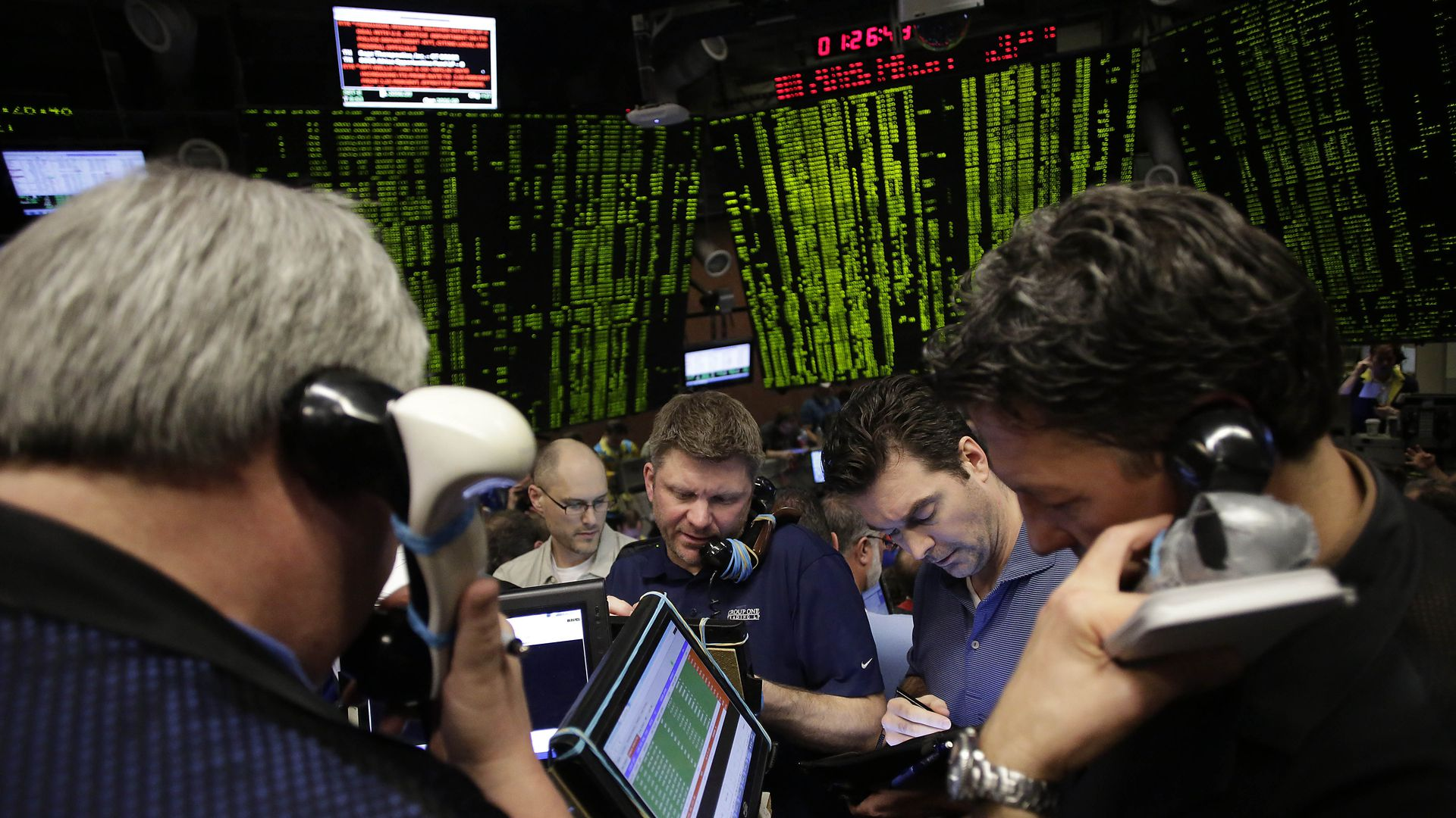 In this image, traders work at the stock market floor and take calls.
