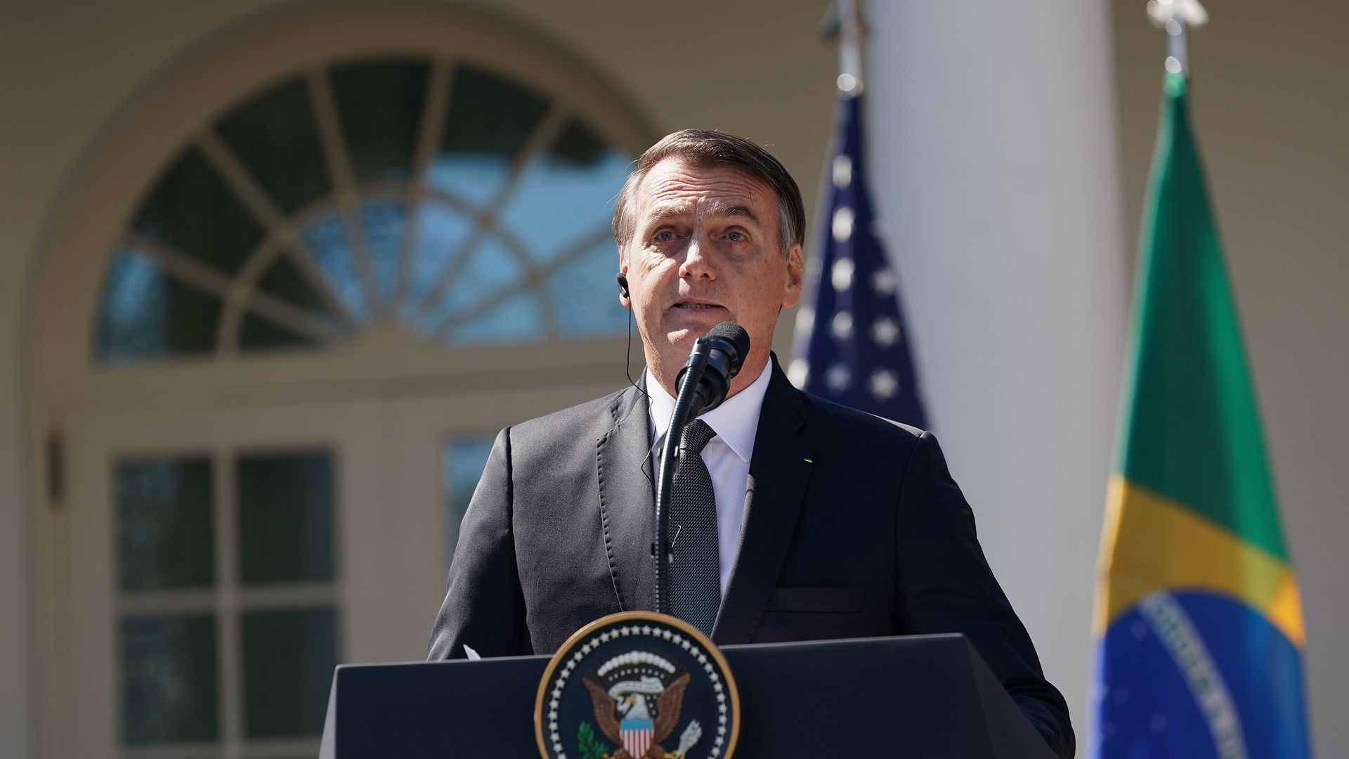 Brazilian President Jair Bolsonaro is pictured here speaking at a podium at the White House, with an American and Brazilian flag behind him.