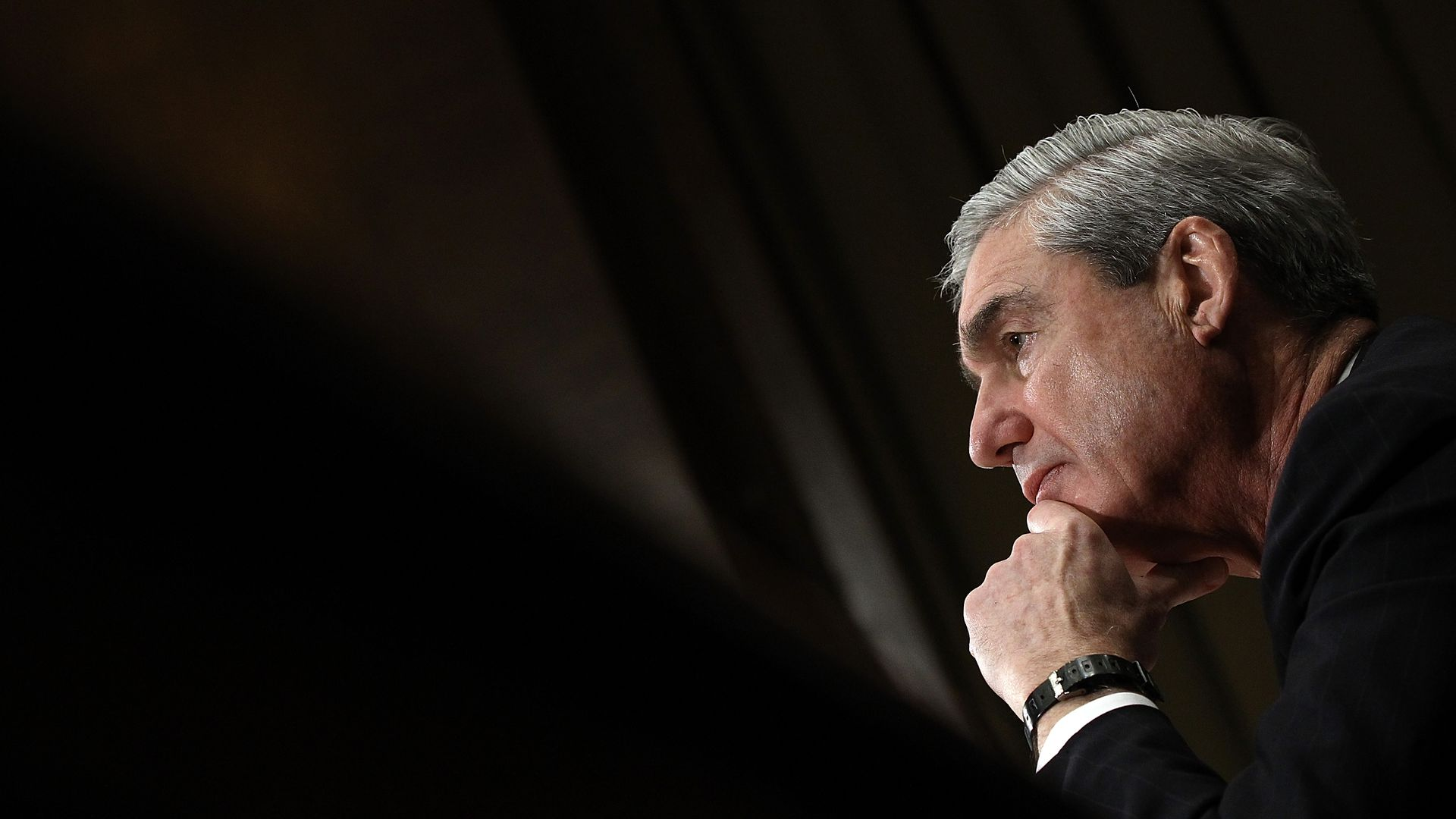 In this image, Robert Mueller looks to the left while resting his chin on his hand.