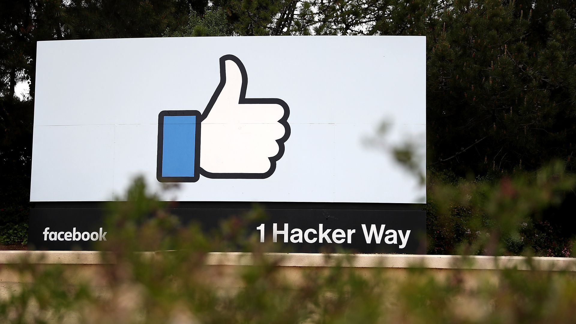 "Photo of billboard outside Facebook headquarters with ""like"" icon and ""1 Hacker Way"" address"