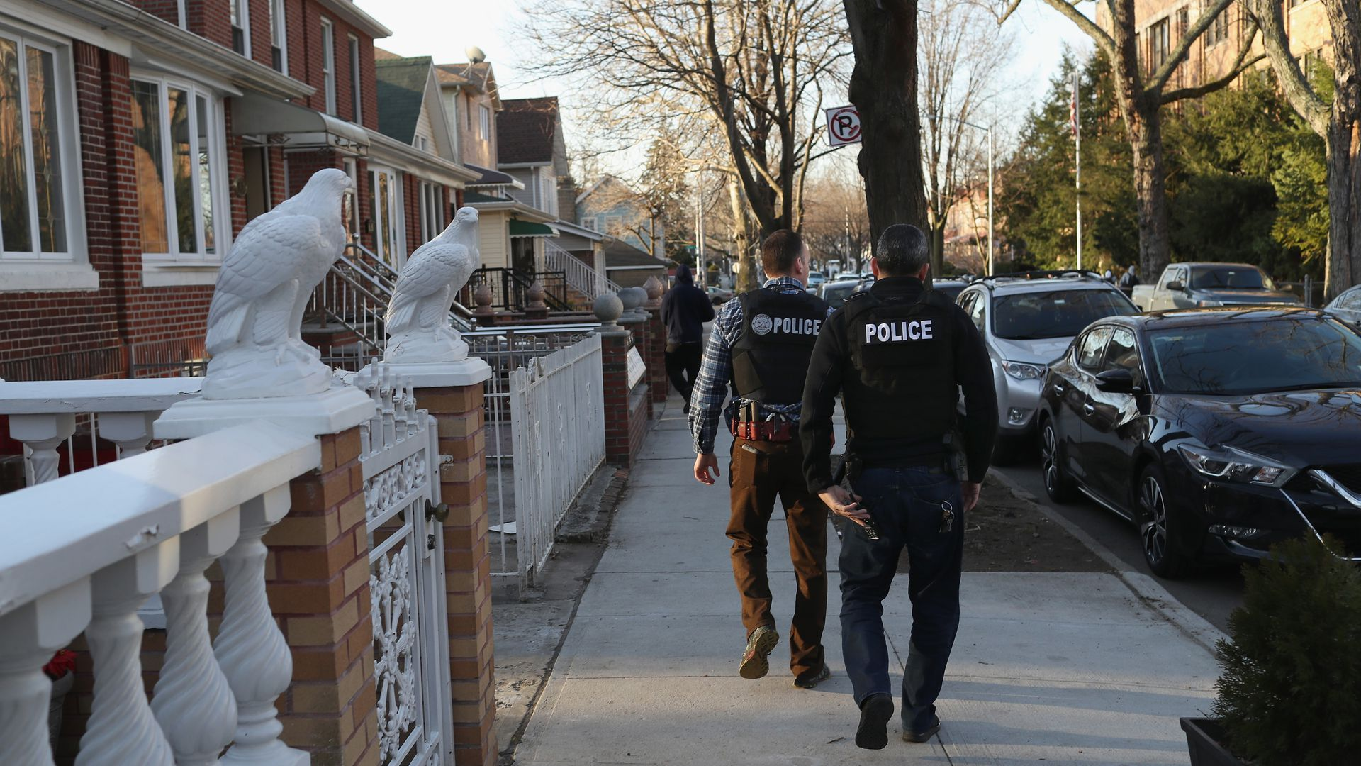 Two police officers walk through a neighborhood