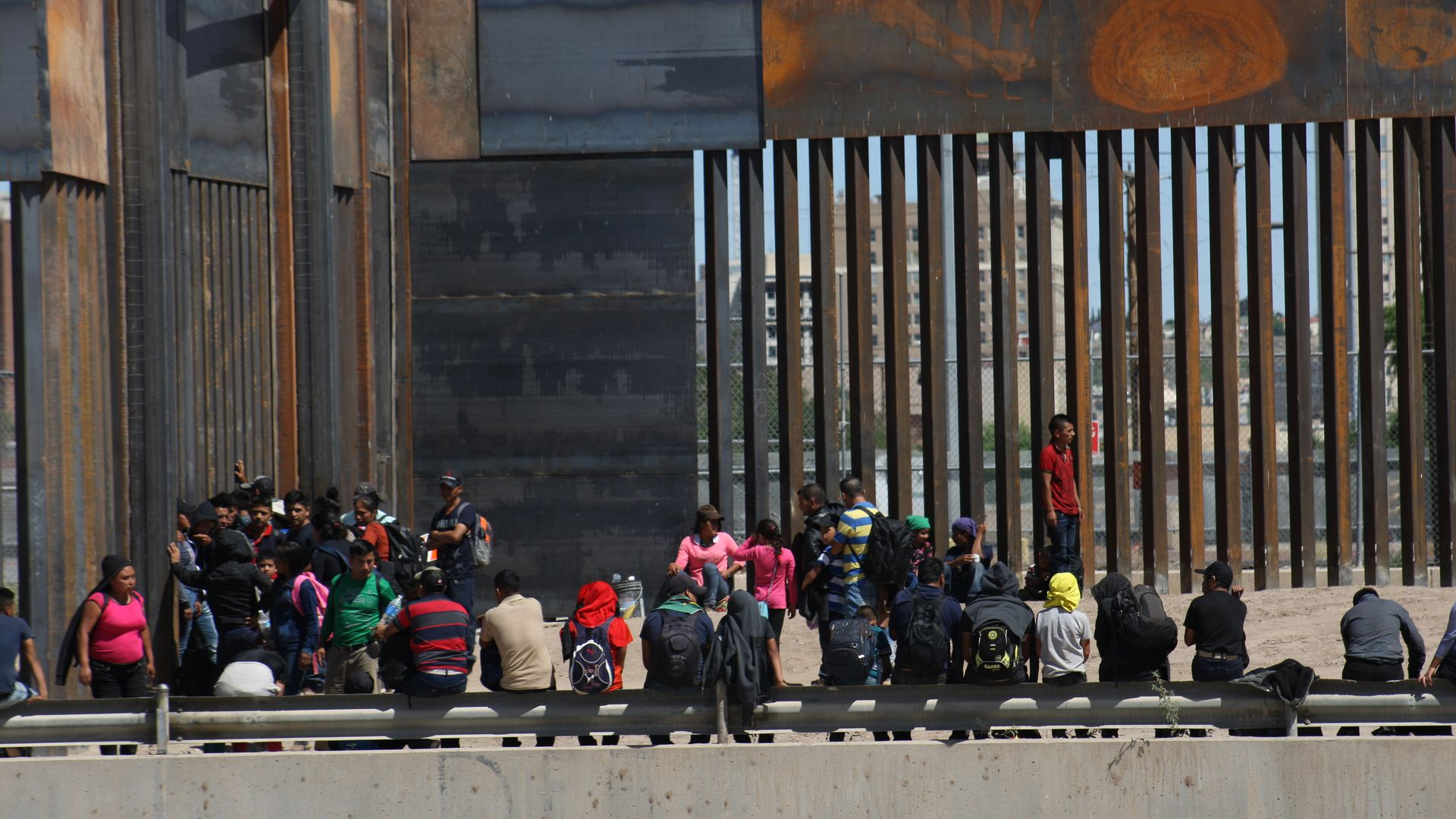 A crowd of migrants standing and sitting outside of a large border fence on the southern border.