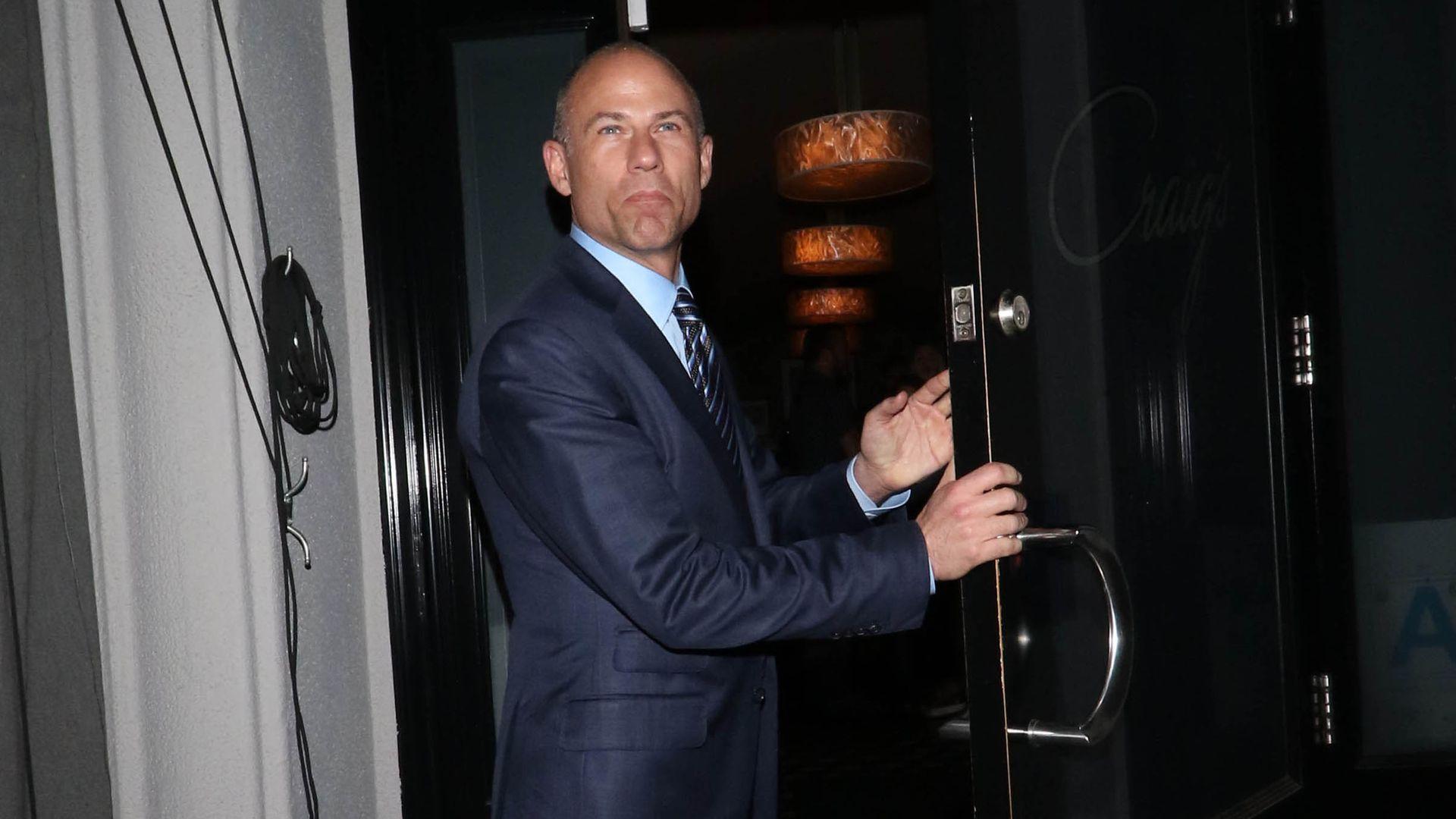Michael Avenatti stands in a doorway holding a door open