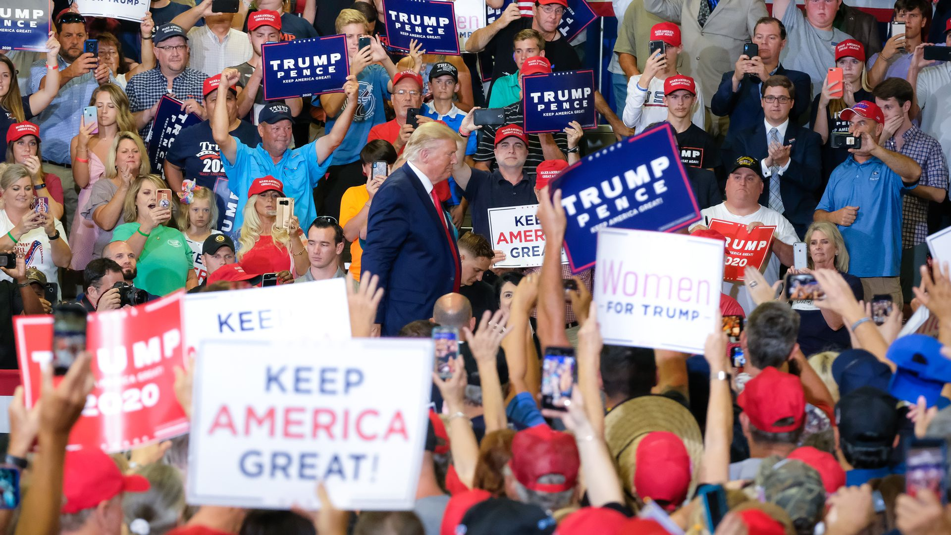 Trump walks through a crowd holding Trump Pence signs at a rally.
