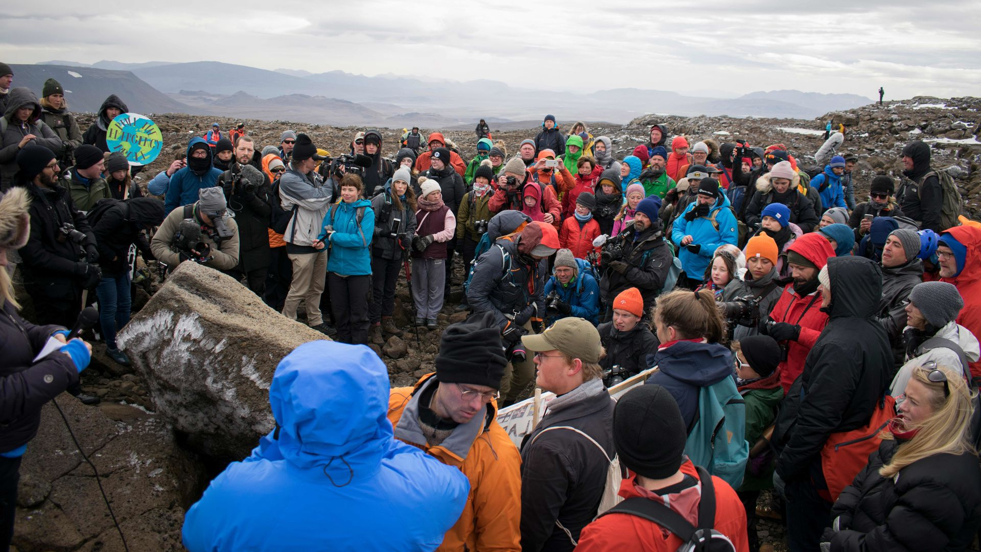 People gathering around a makeshift memorial for the glacier. Photo: JEREMIE RICHARD/AFP/Getty Images