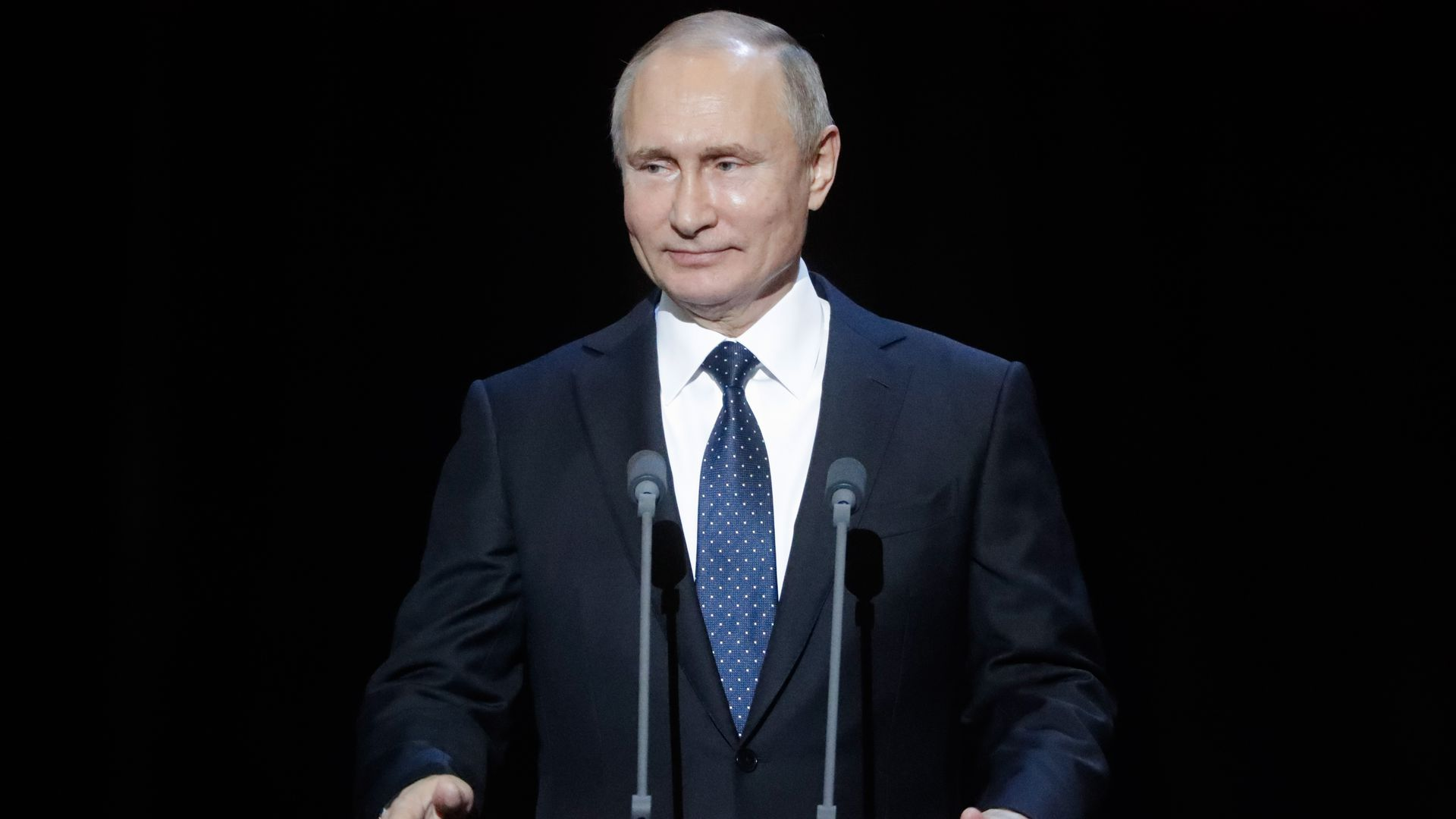 Vladimir Putin at podium smiling.