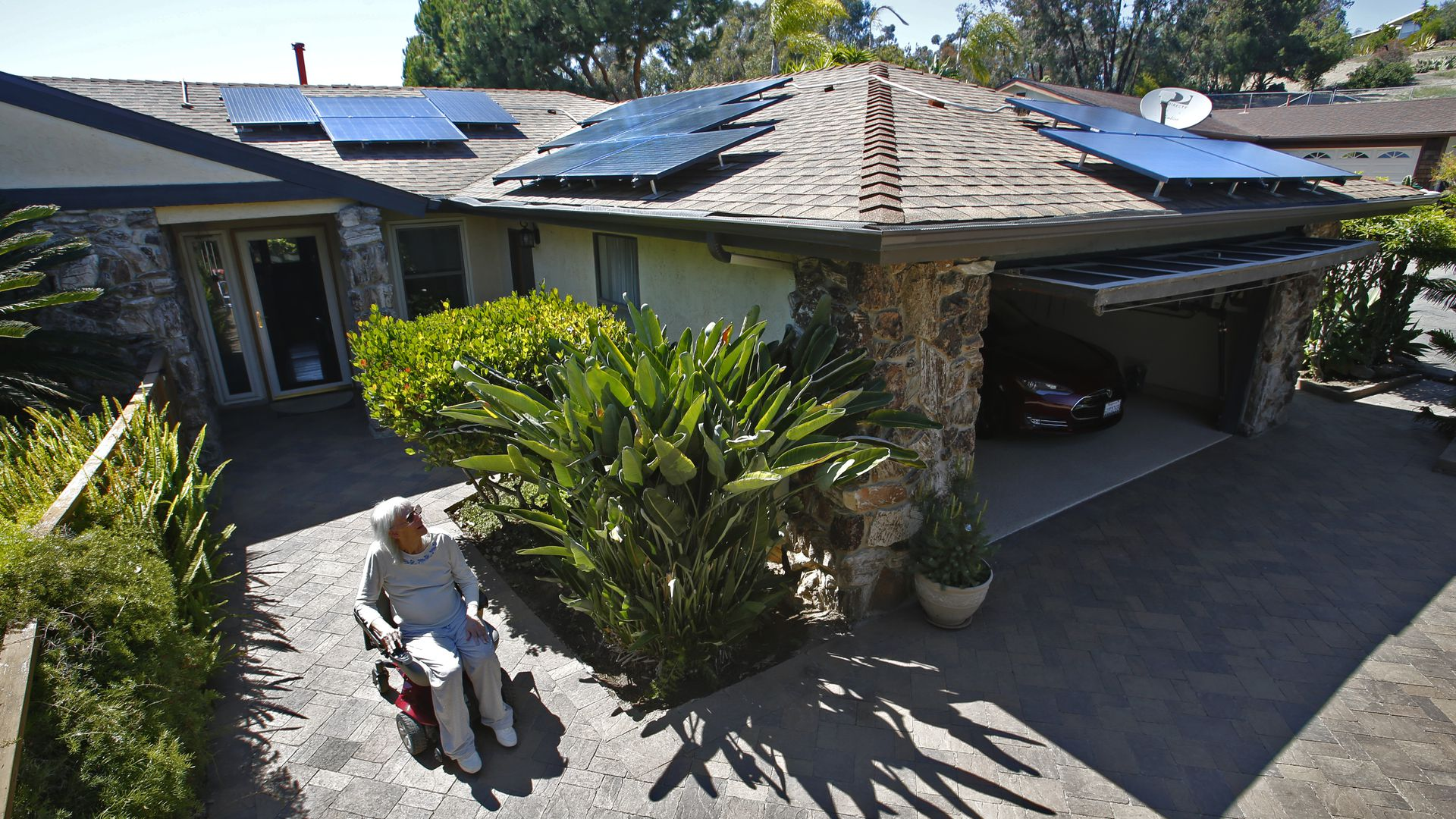 Woman cruises around her Oceanside home that has enough solar collectors on the roof to charge her wheelchair, her electric car and run all the household appliances.