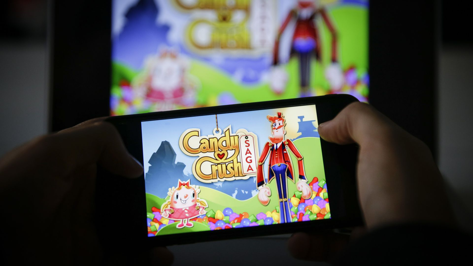 In this image, someone holds a phone that displays the Candy Crush home page in front of a TV screen that also displays Candy Crush.