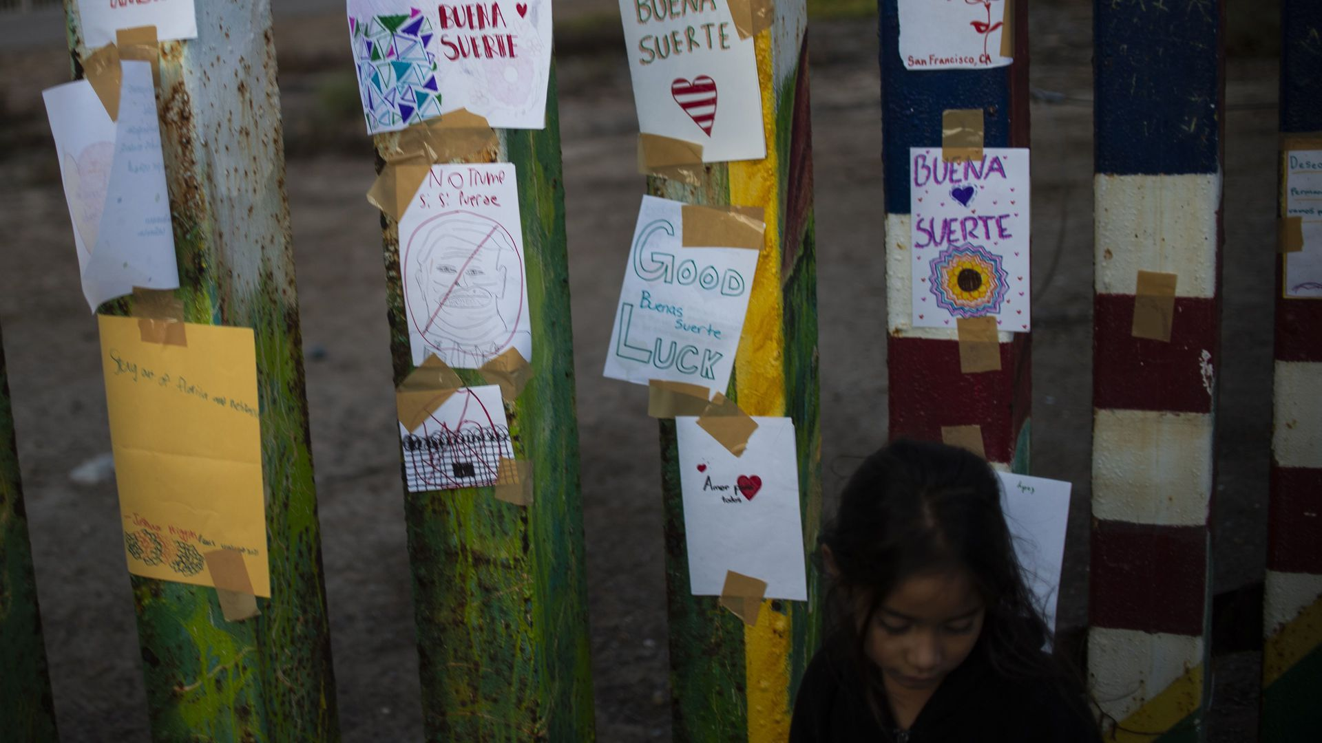 A young girl stands next to messages tacked to the US-Mexico border